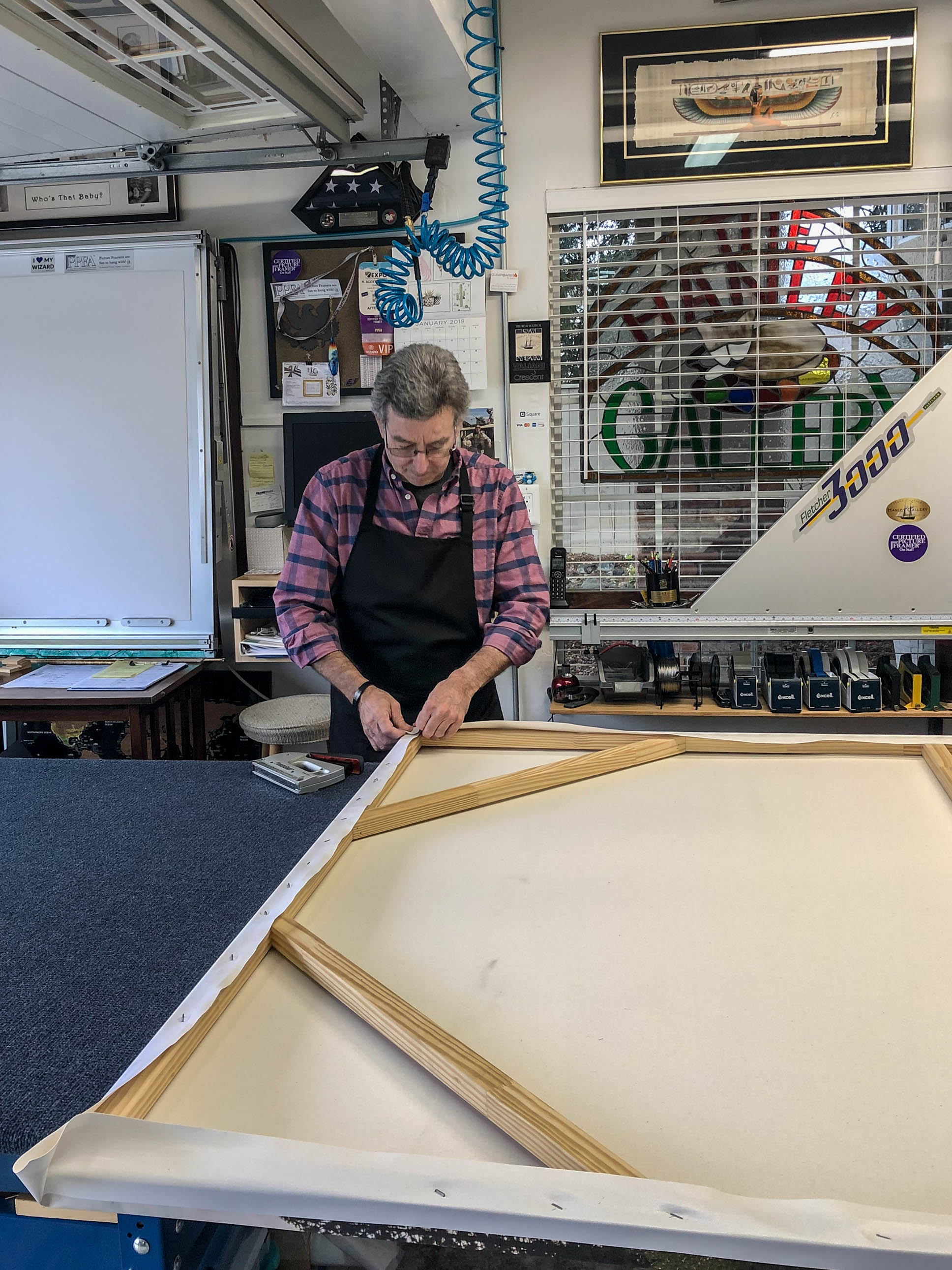 The canvas being attached to the frame.