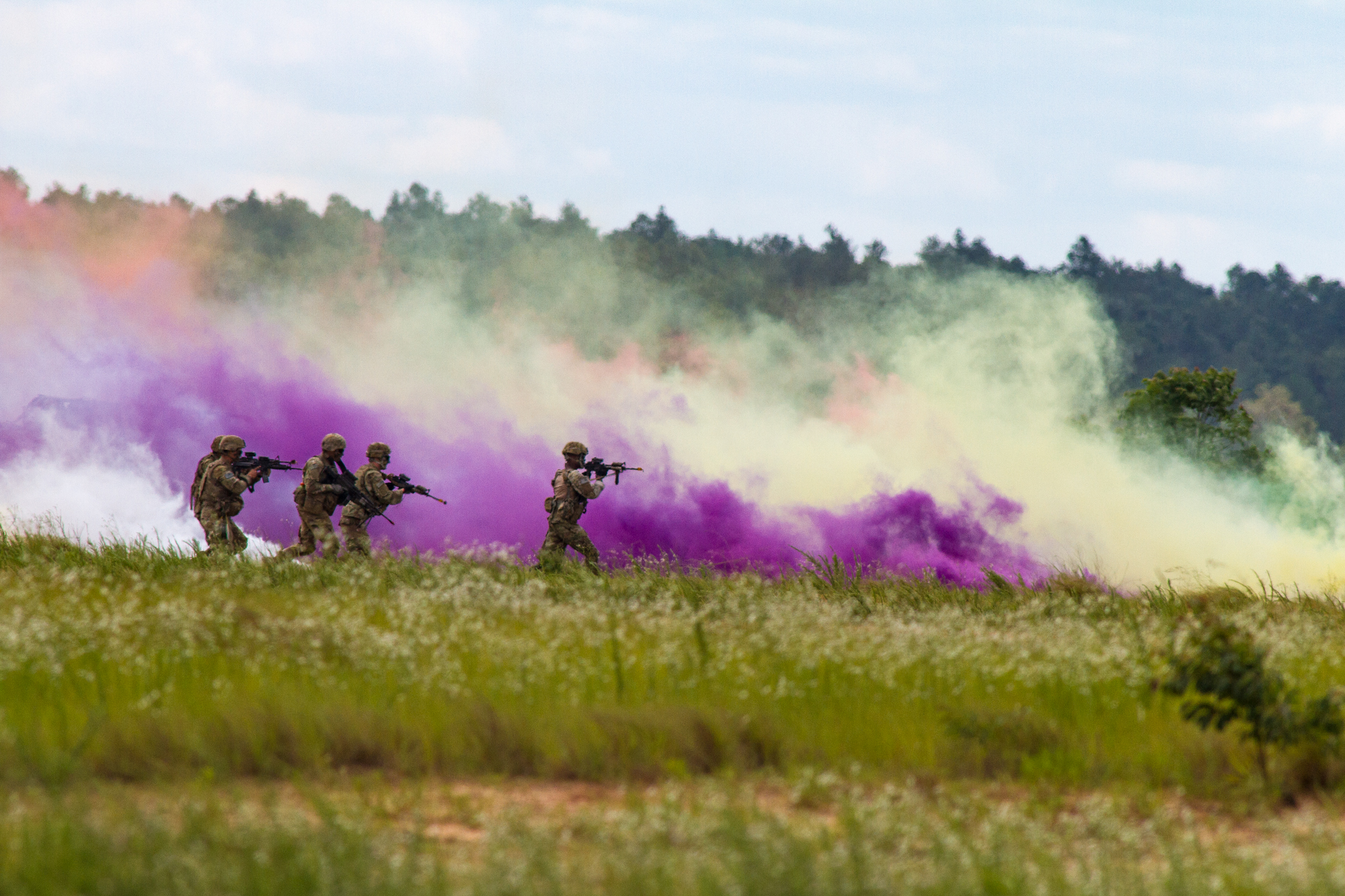 Paratroopers from the 82nd Airborne Division simulate an assault of a compound under cover of smoke as part of the Airborne Review at Sicily Drop Zone at Fort Bragg, N.C., on Thursday, May 25, 2017.