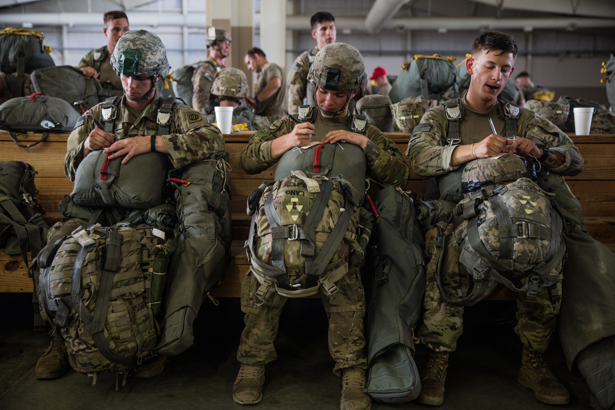 Paratroopers Talbert, Lang and Capik of the 82nd Airborne Division write their name, rank, and unit on name cards before an upcoming training jump at Fort Bragg, N.C. on July 26, 2017.
