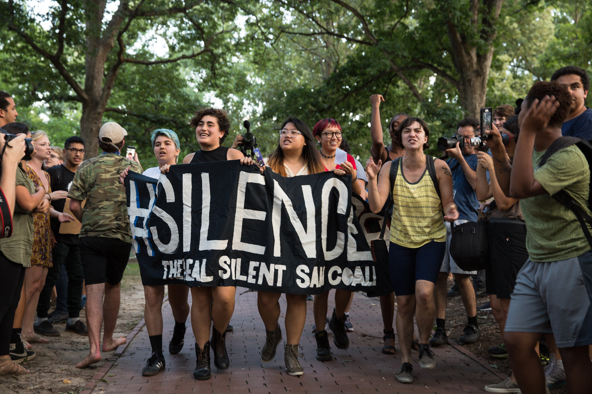 From left to right, Cosima Hernandez, Suad Jabr, Emily Yue and Mitch Xia carry a Real Silent Sam Coalition banner as they marched in protest against the statue at the University of North Carolina at Chapel Hill. Protestors for and against the statue's removal attended rallies near the monument on Tuesday, August 22, 2017.