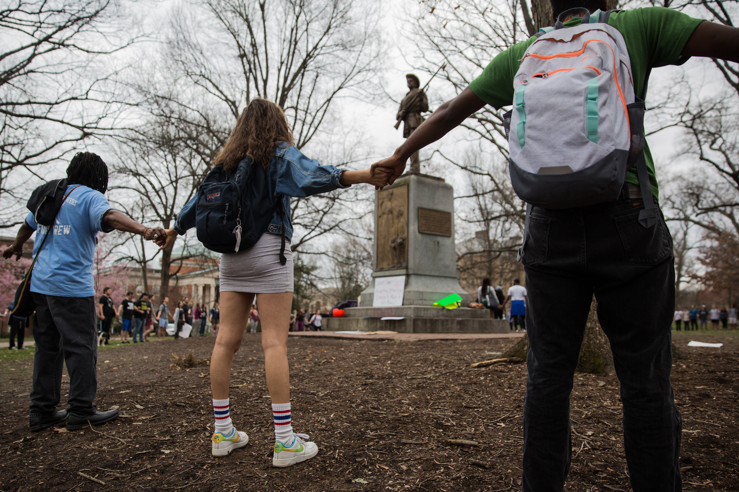Students gather and hold hands in a circle around the Silent Sam monument at the University of North Carolina at Chapel Hill. A large demonstration formed around the statue to protest the statue's position on the university's campus on February 21, 2018.