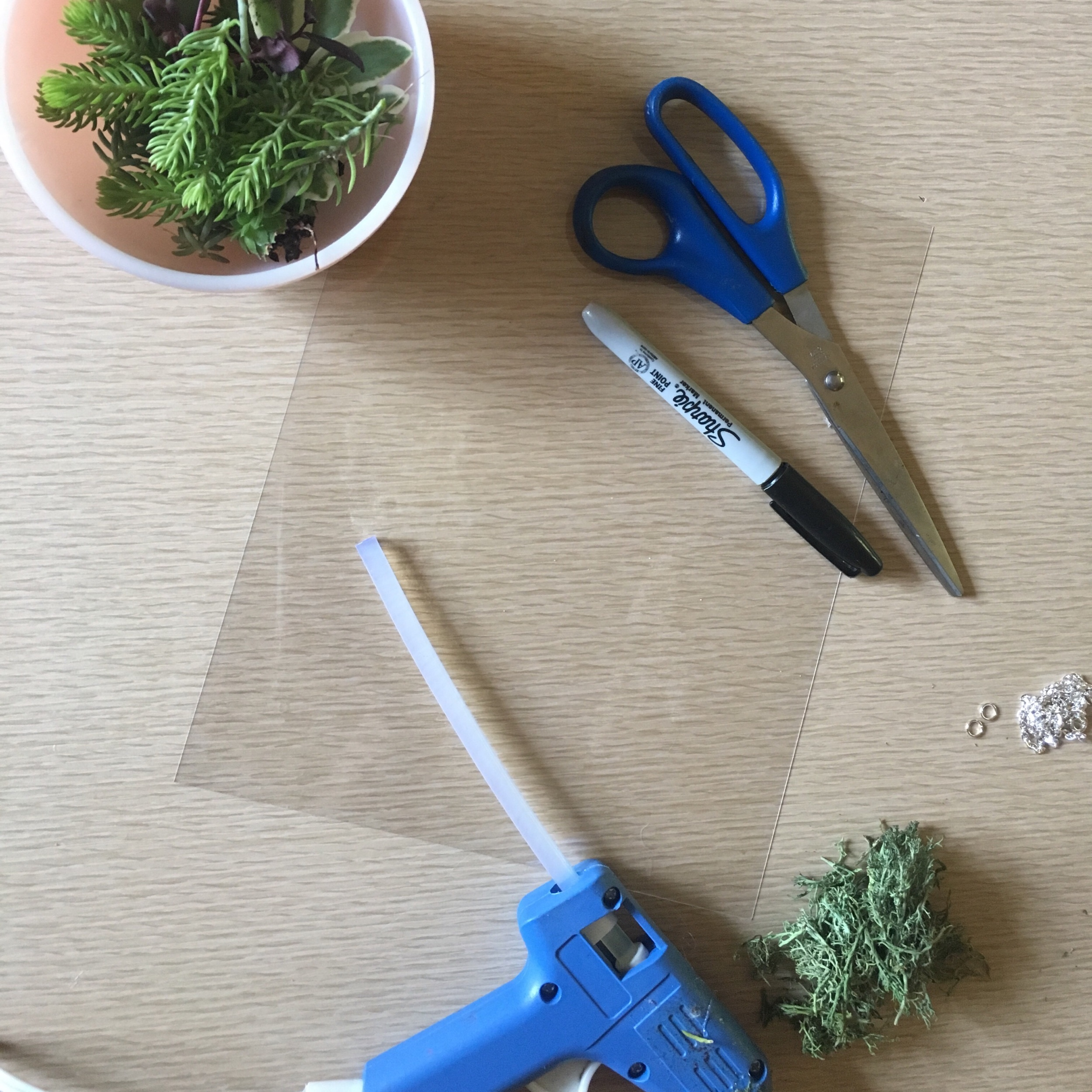 Step two: gather or purchase this stuff- some reindeer moss (or other preserved moss), a chain and closure, jump rings, a piece of shrink film, scissors, a sharpie and a hot glue gun (with glue). You will also need a hole punch, needle nose pliers, oven and baking tray of some kind. Preferably vintage Jadeite but IDK.  I also really like to add little crystals or fancy stones, but not today.