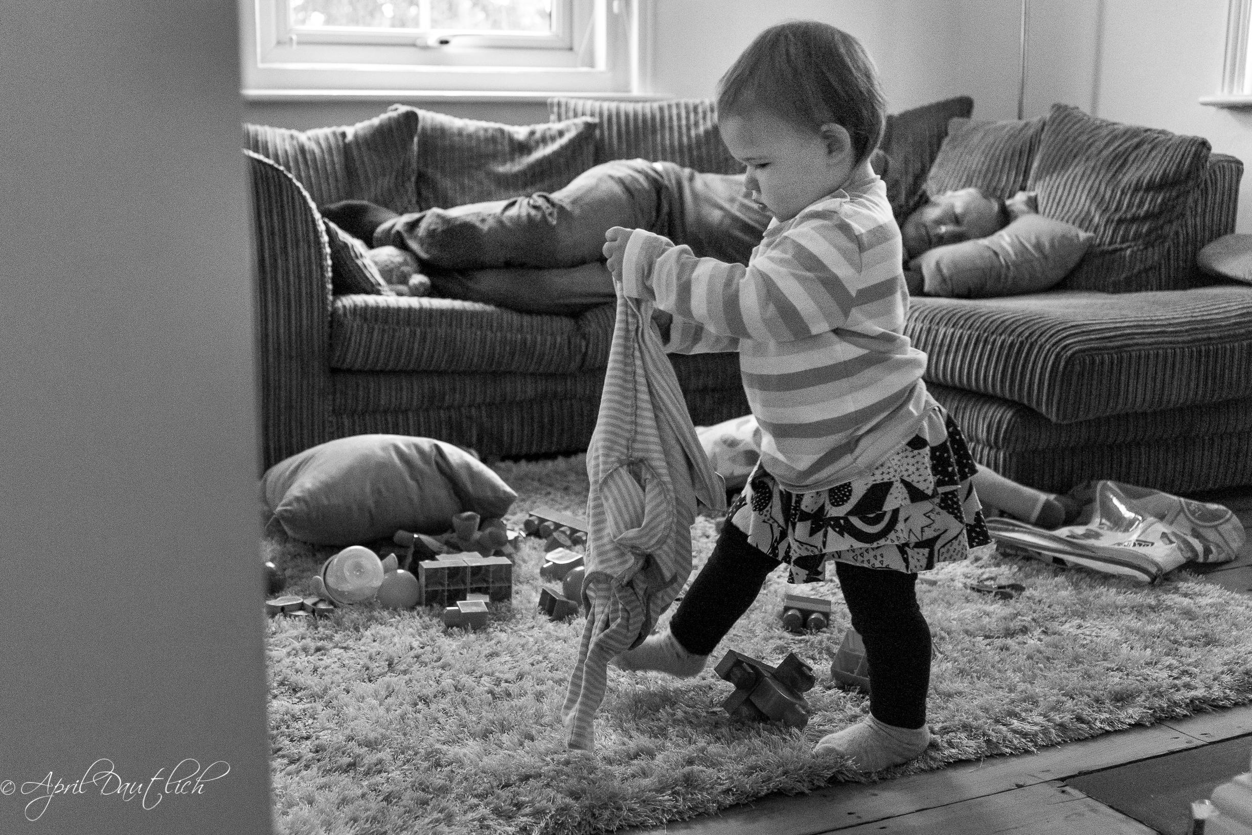 Family photography. Baby stomping through chaos while dada sleeps on the sofa.