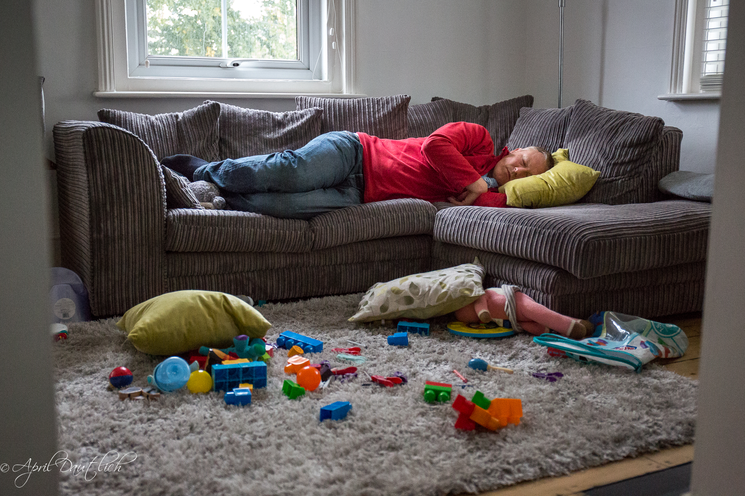 Dada napping on the sofa in the middle of toy chaos.