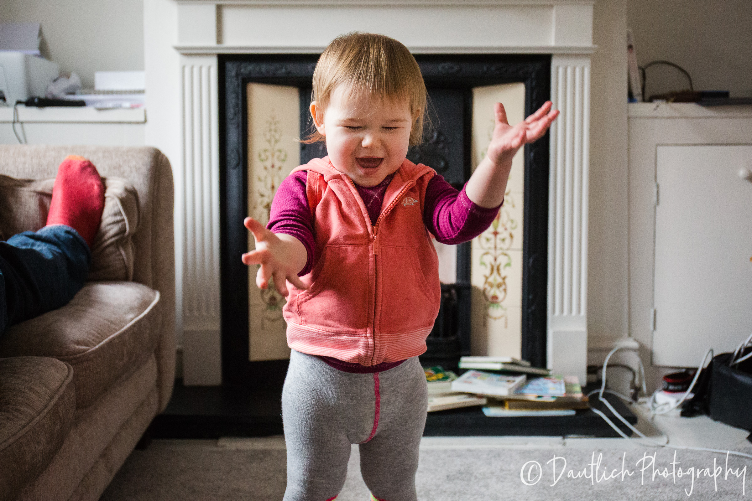 Toddler Hazel laughing as she tosses a stuffed elephant into the air.