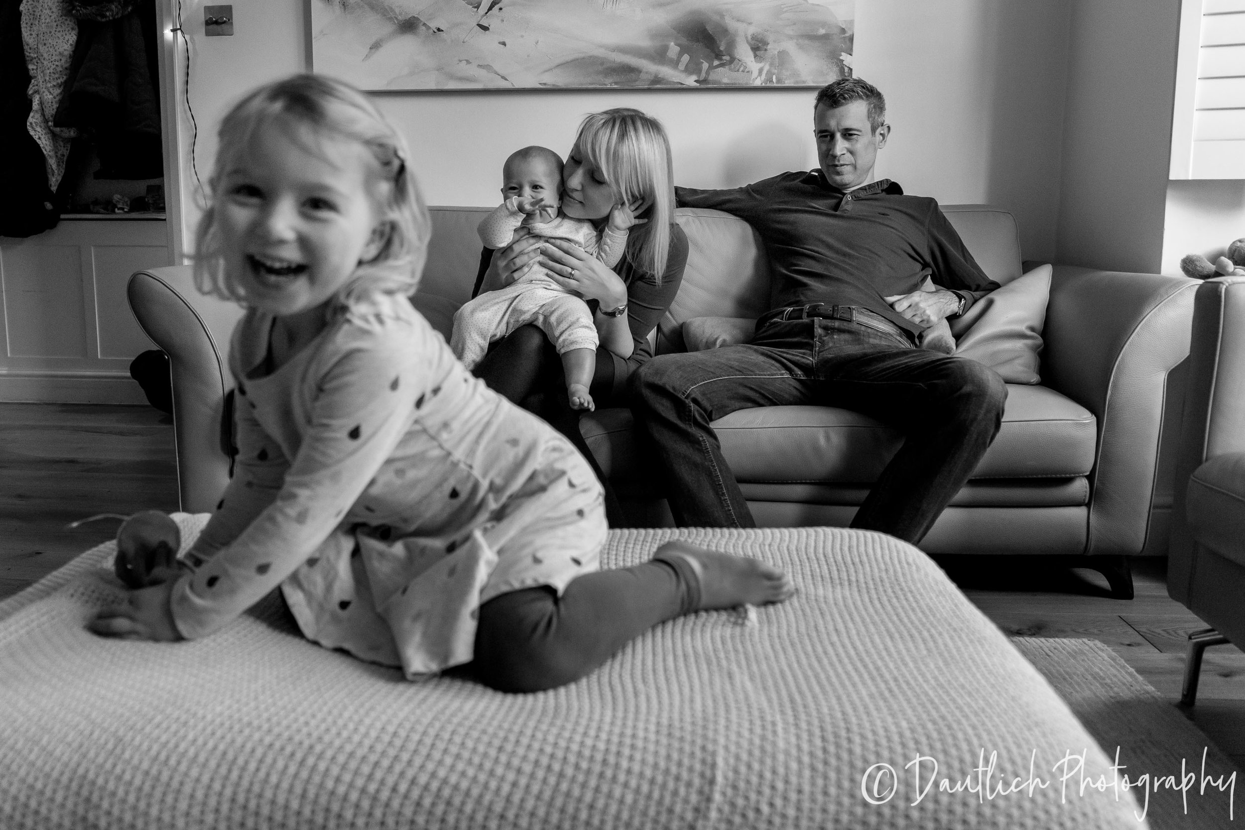 The apostolov family on the sofa with 3 year old Lila jumping on the footstool.