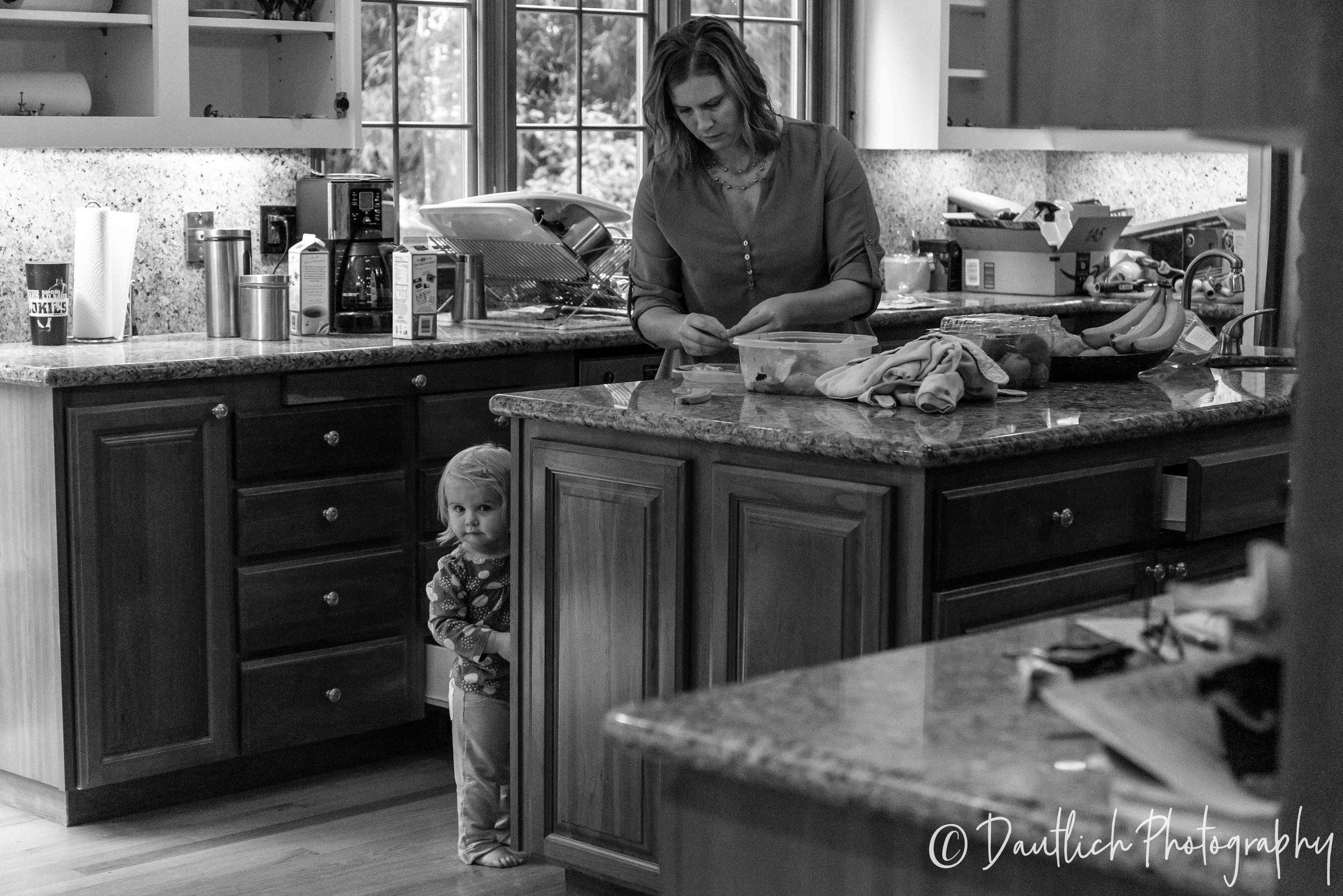 Aina peeking around the corner from the kitchen island as mom prepares some snacks.