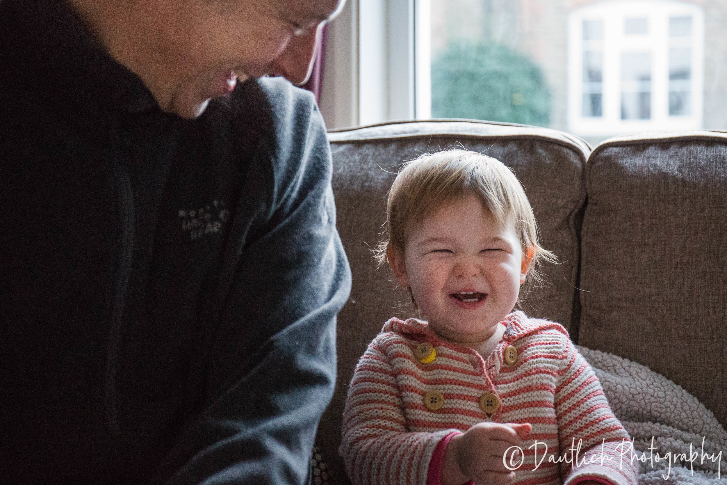 Toddler and dada laughing on the sofa together.