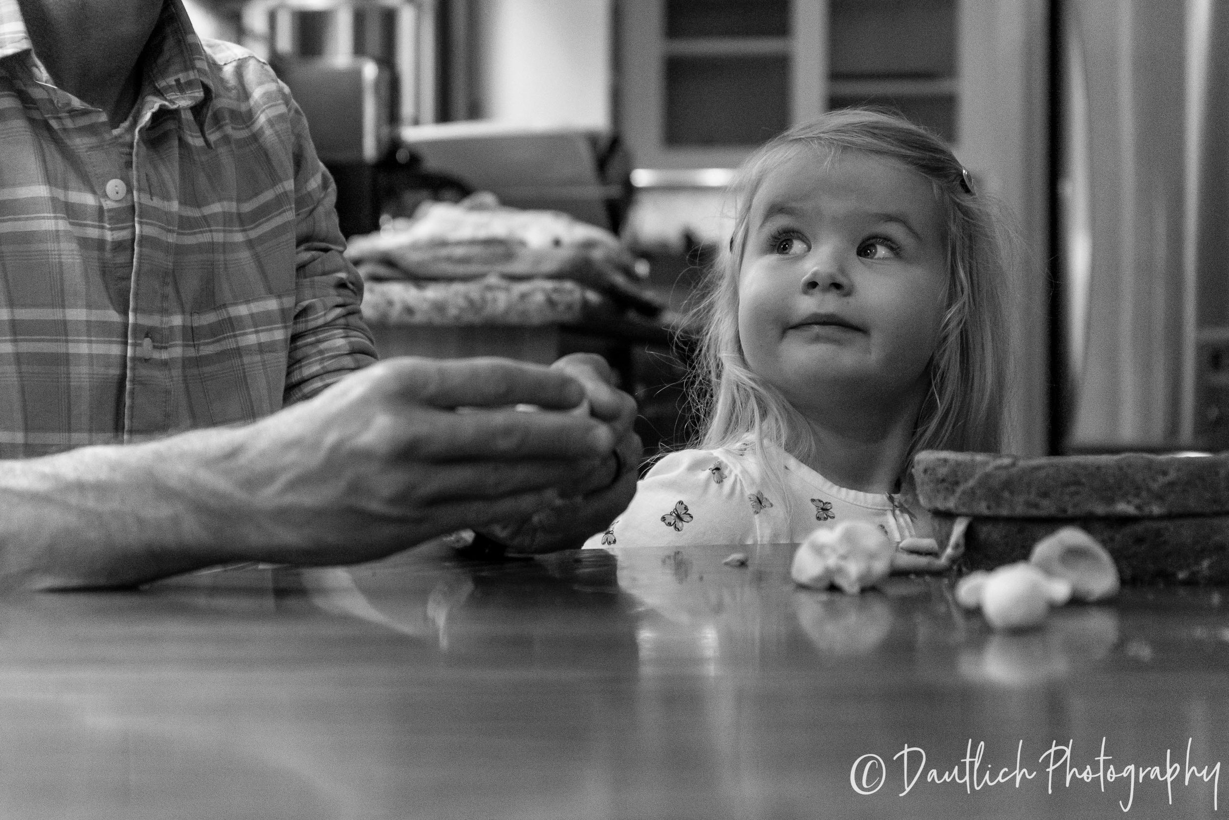 Toddler makes a silly face at dad as he makes figures out of fondant.