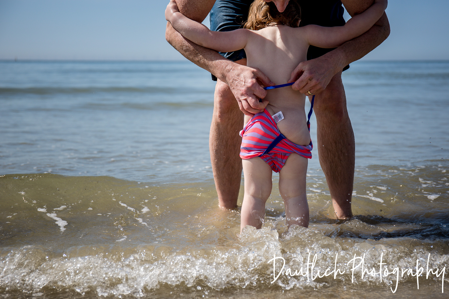 Nick is pulling Hazel's swimsuit up in the cold English Channel at Shoreham by Sea on a sunny day in June.