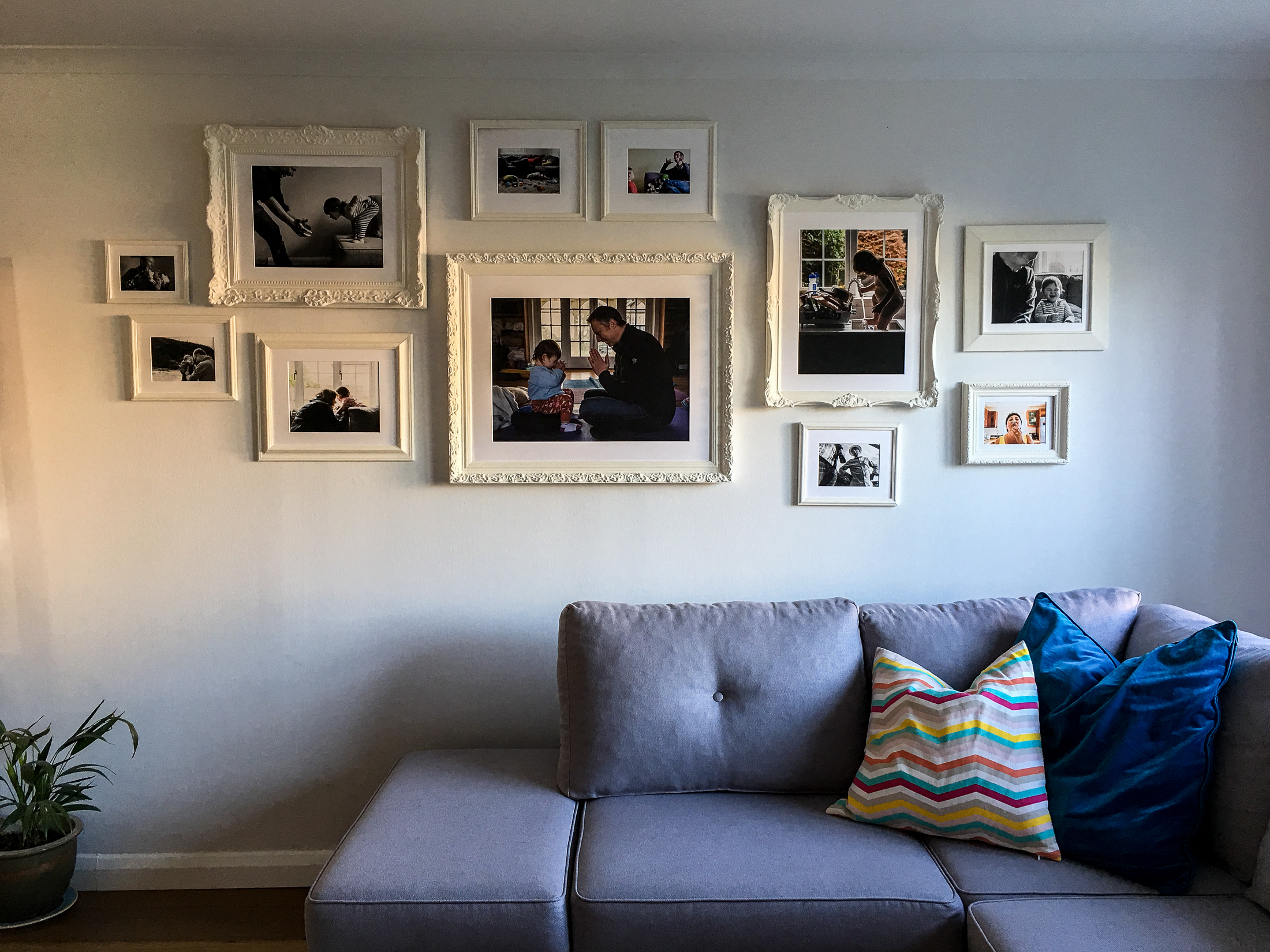 Upcycled wall gallery with old frames refinished and painted white.