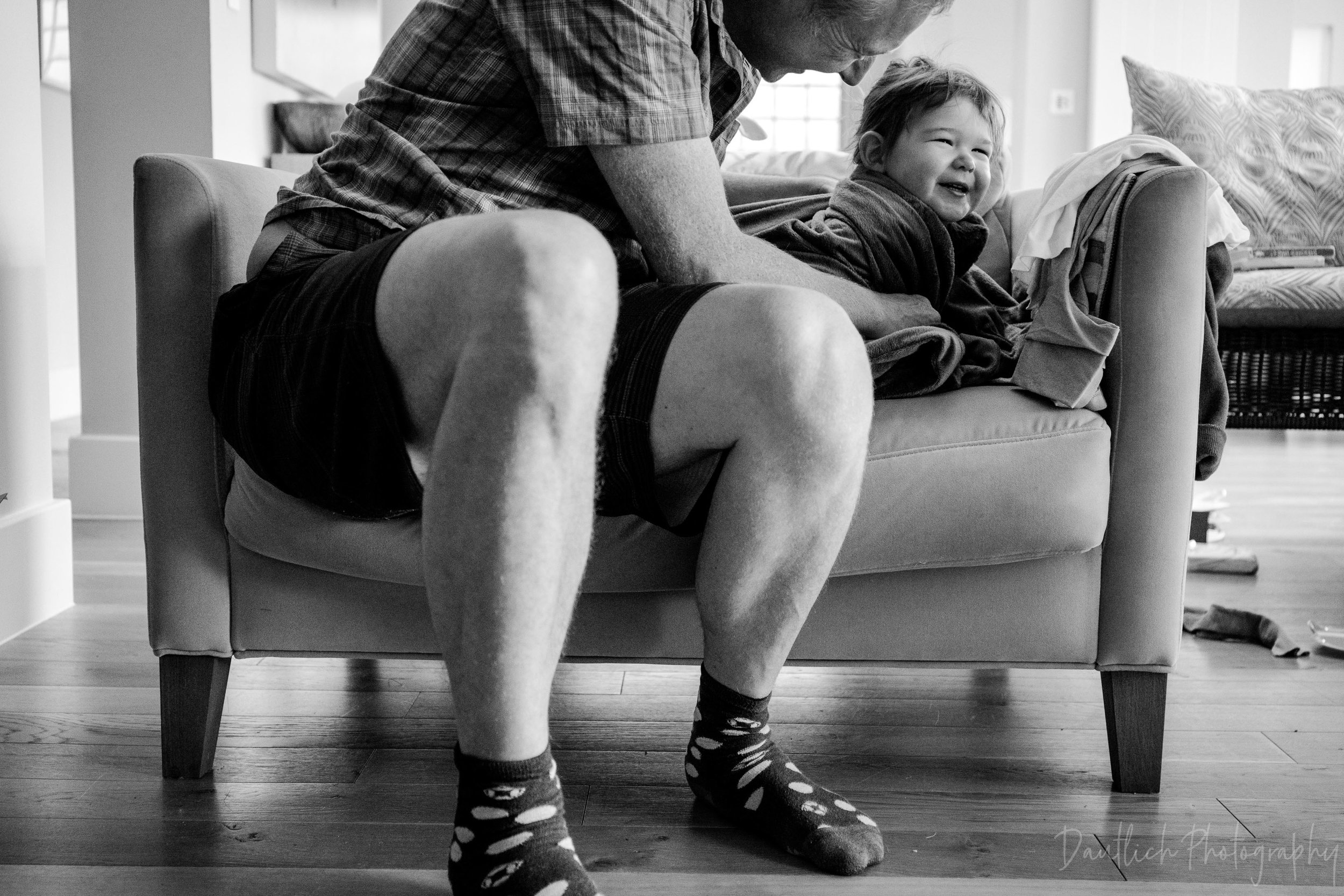 Dad tickles toddler in a chair with affection and sweet laughter.