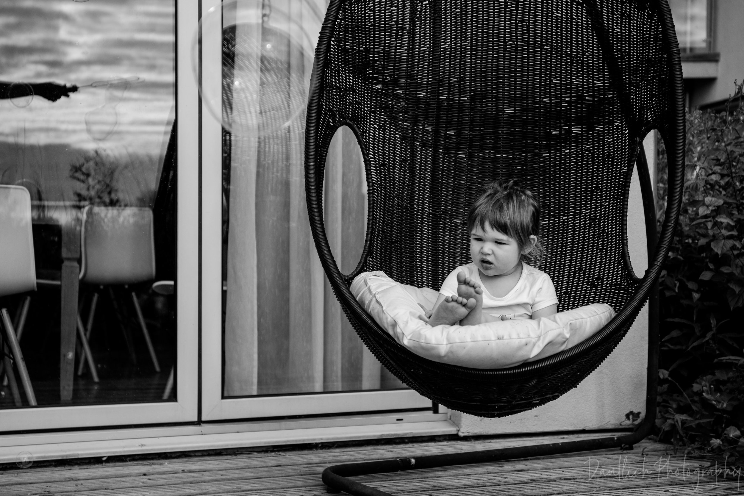 Toddler sits in egg chair while dad blows bubbles toward her.