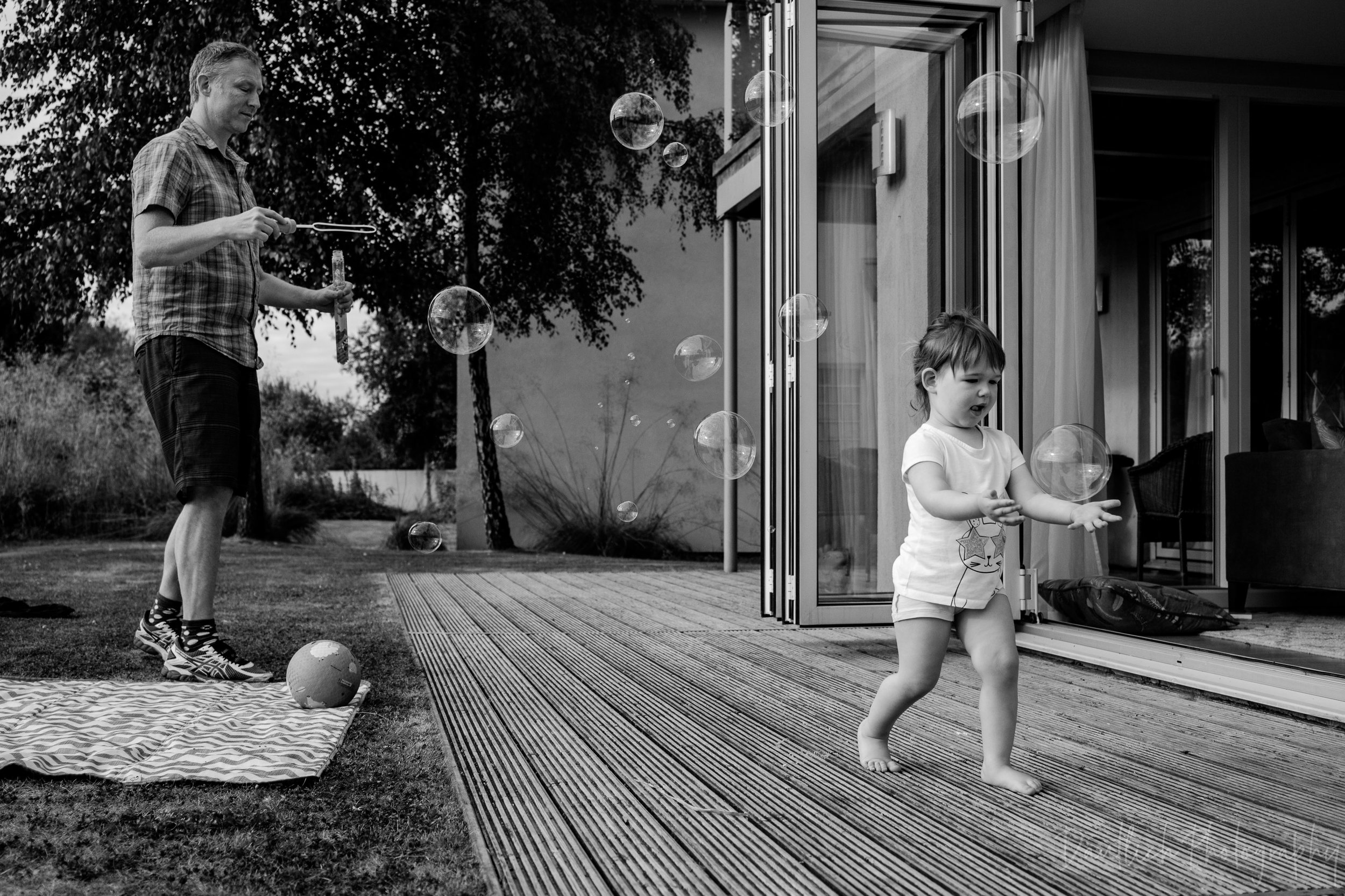 Toddler chases bubbles on the back patio.