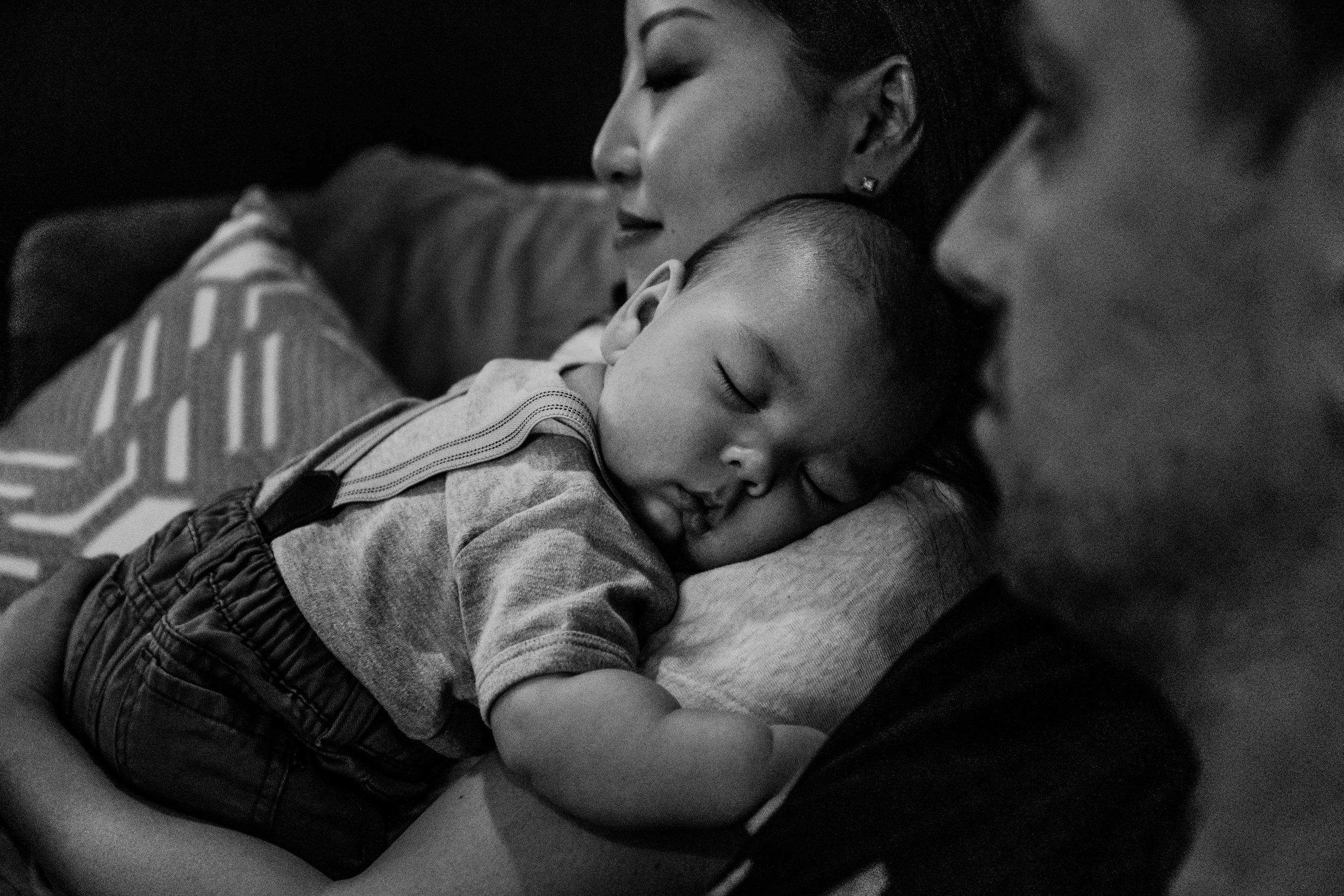 Baby boy sleeping on mum's shoulder while she soaks in a quiet and peaceful moment with dad by her side.