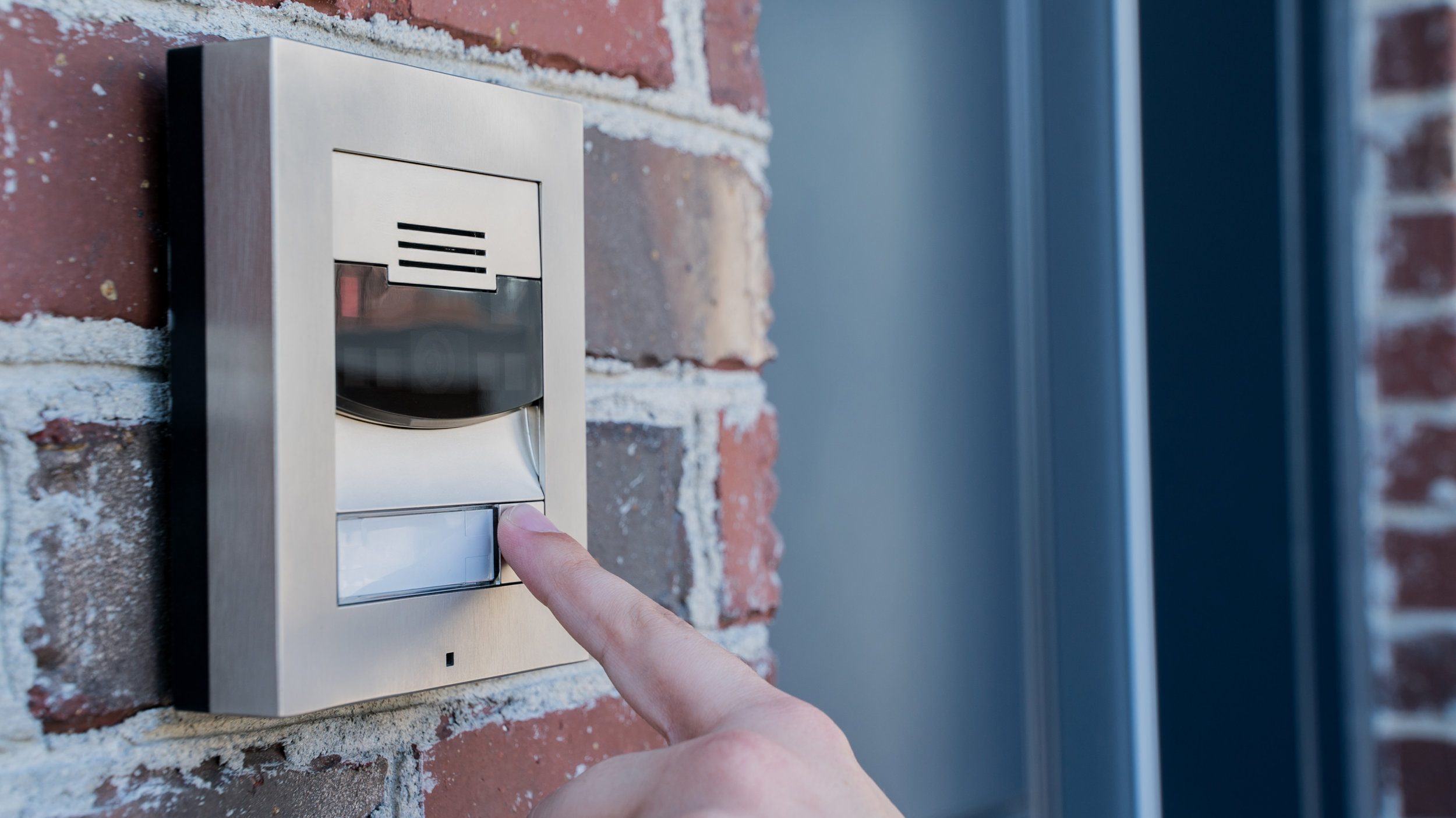 Smart_Home_Security_Video_Doorbell_Control4_Intercom_Anywhere_Red_Brick_Wall_Person_Pressing_Button