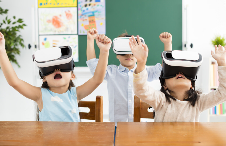 Three_Children_in_Classroom_Wearing_Virtual_Reality_Headsets_Hands_in_the_air_Joy