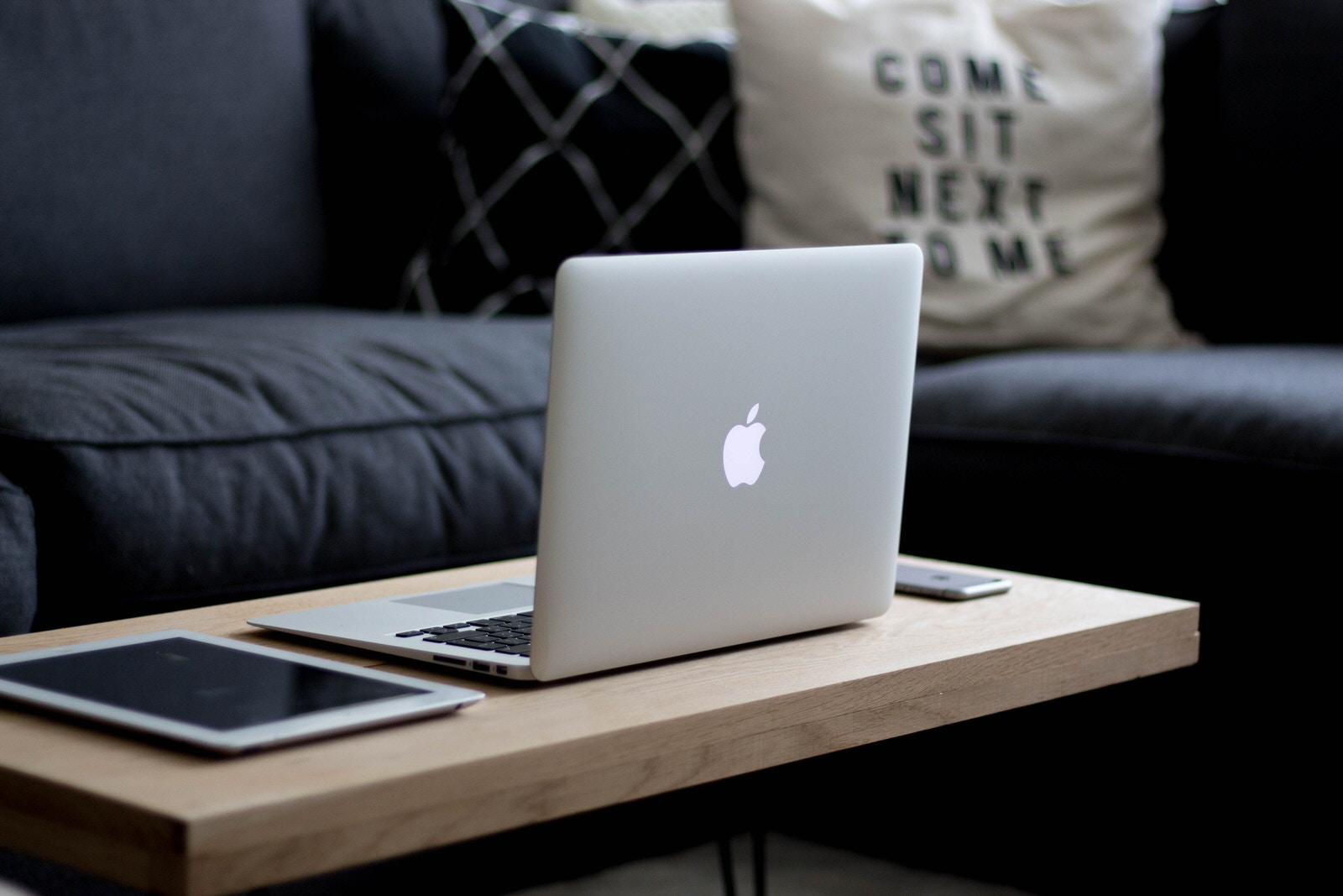Home_Networks_Mac_Book_Air_Silver_iPad_iPhone_on_Brown_Coffee_Table_Dark_Blue_Sofa