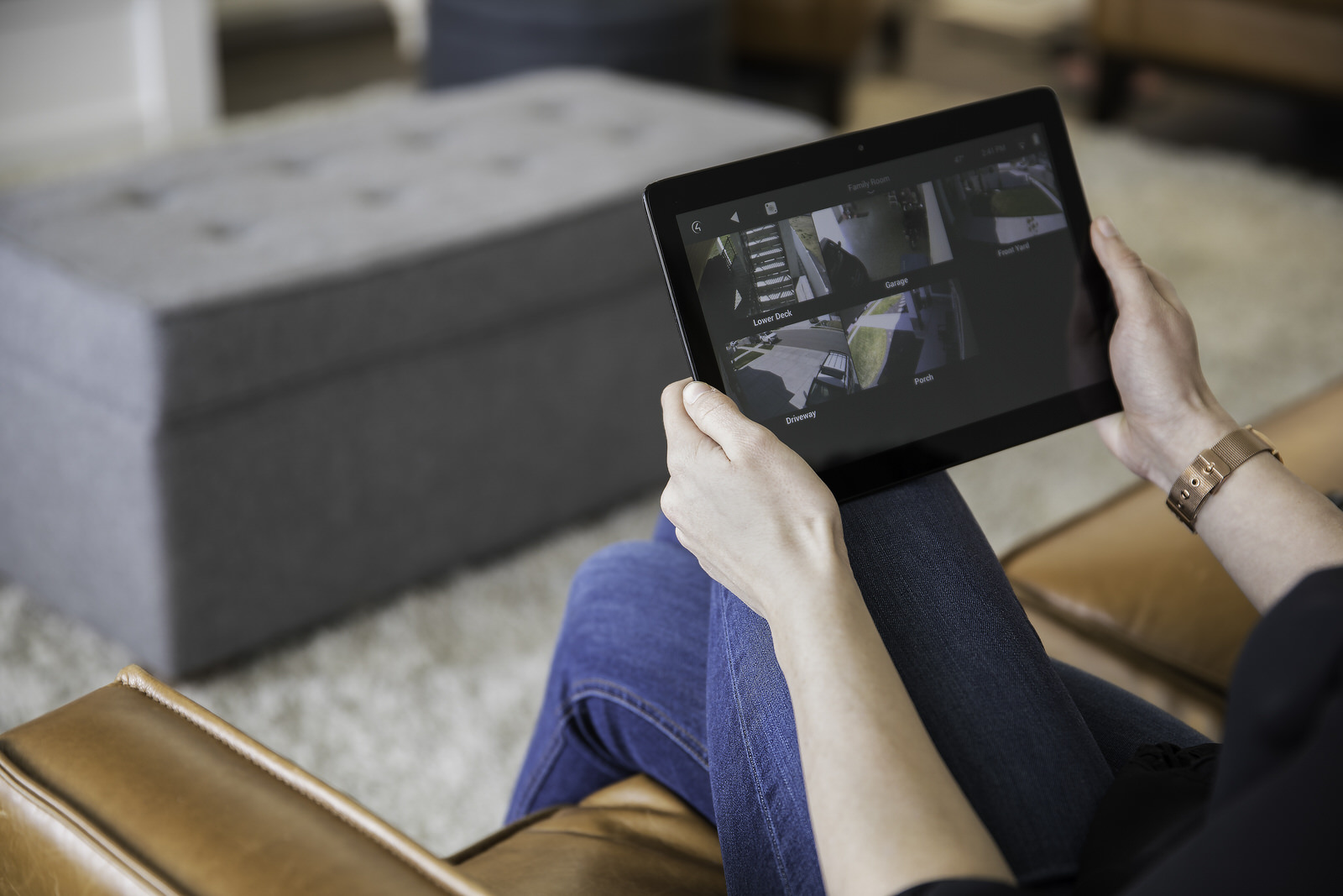 Smart_Home_Security_Man_Sitting_On_Brown_Sofa_Holding_iPad_Watching_Video_CCTV_Camera_Surveillance_Blue_Jeans_Grey_Rug