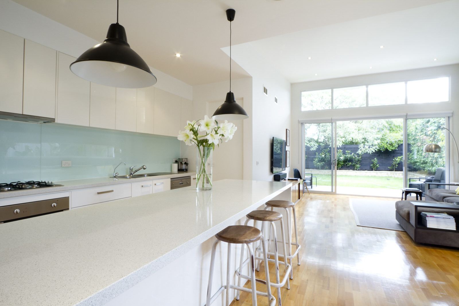 Lutron_Lighting_Kitchen_Diner_White_Cabinets_Glass_Splashback_Brown_Flooring_Leading_To_Garden_Black_Fence_Wall_Mounted_Smart TV.jpeg