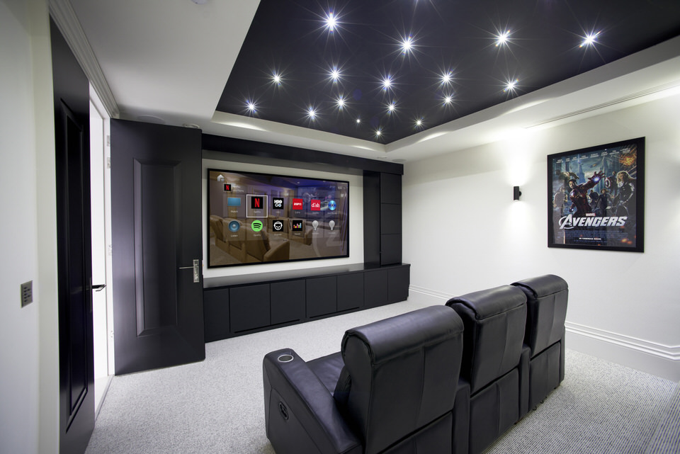 Control4_Home_Cinema_Room_Navigators_On_Screen_White_Walls_White_Carpet_Black_Cabinetry_Seats_Avengers_Poster_OS3_Operating_System