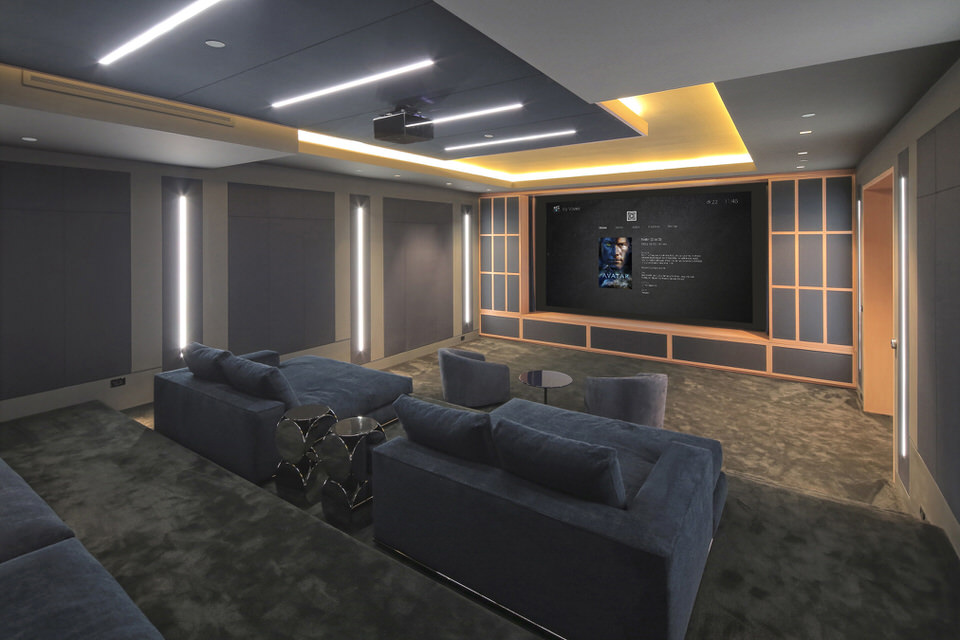 Control4_Home_Cinema_Room_Grey_Carpets_Seats_Blue_Seating_White_Lighting_Pine_Effect_Cabinetry_Avatar_Film_On_Screen_OS3_Operating_System