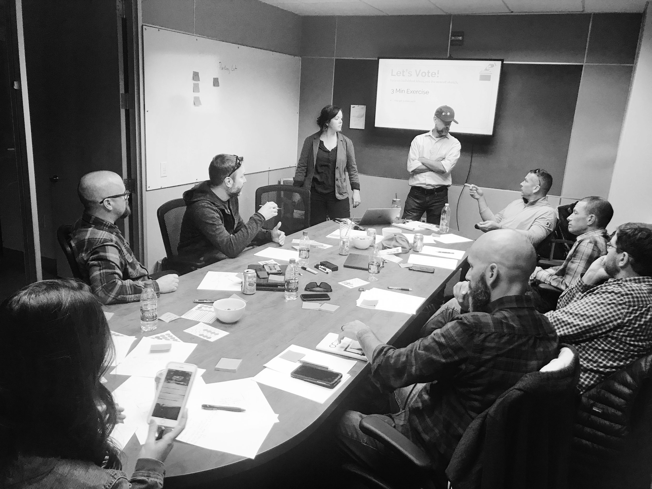 Facilitating workshop which included 10 participants: co-designer, product manager, CTO, director of implementation, senior sales manager (not pictured), two current customers in pilot and three potential customers.