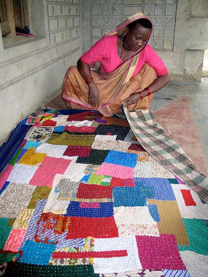 Quilter examining sari backing,Kendalgiri village