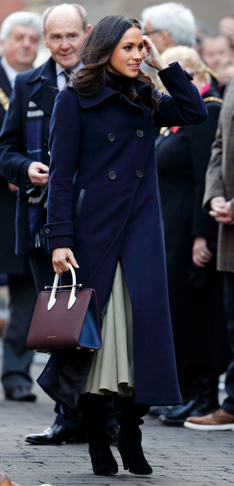 Meghan attended her first public appearance with Prince Harry in Nottingham wearing an all-British/American fashion ensemble comprising of a double-breasted Mackage navy coat, Joseph skirt and carried a burgundy and navy blue Strathberry handbag.