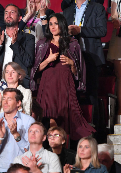 Meghan Markle wore a burgundy pleated dress and matching leather jacket over her shoulders for the opening night of the Invictus Games in Toronto, Canada, September 2017