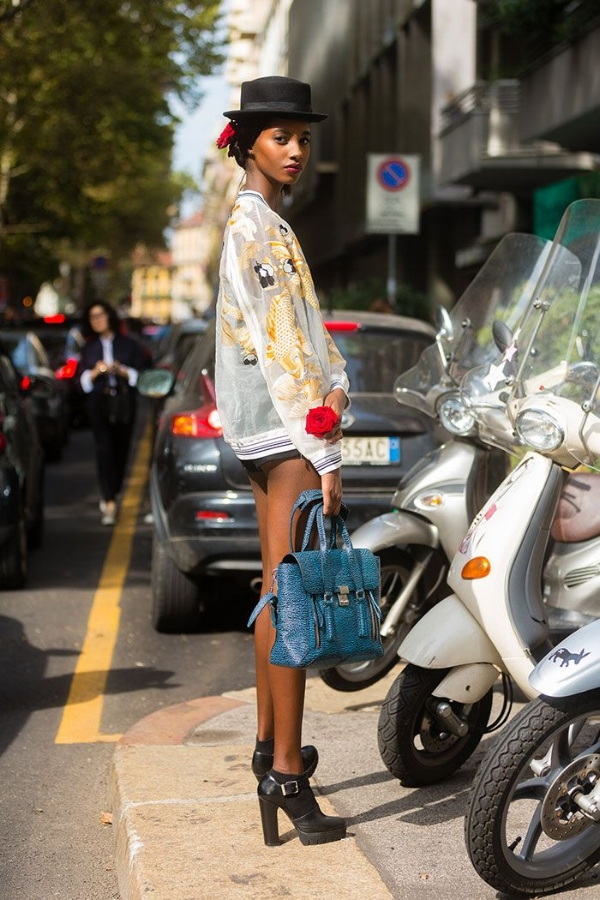 Tami Williams was seen wearing an impressive and original street style look. The model paired a sheer white embroidered bomber jacket with black shorts, black leather ankle boots and a bright blue tote bag. Completing her outfit with a rose in her hair and a black hat, Tami demonstrates how the right accessories can completely change a look via The Front Row View.