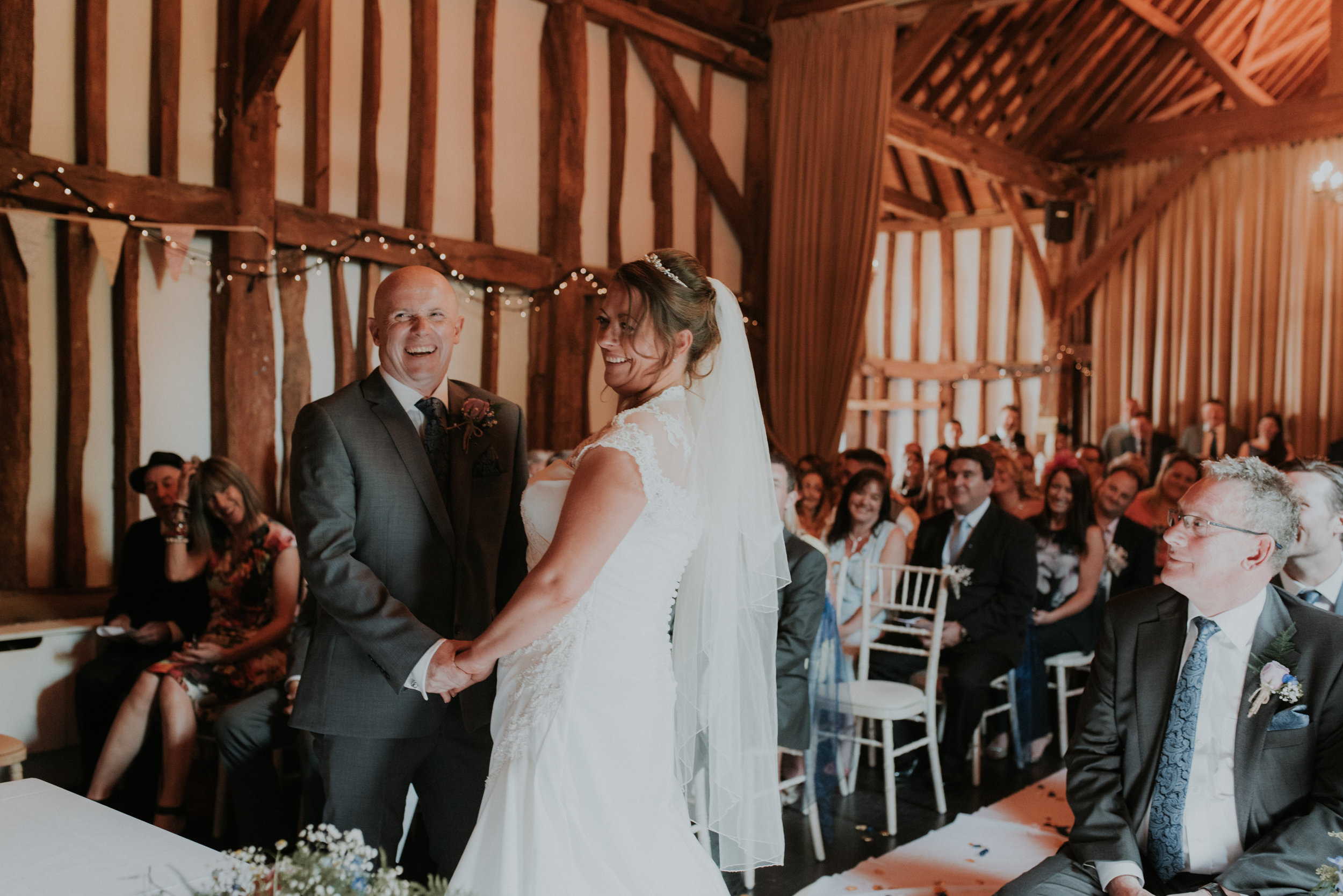 Groom laughing during wedding ceremony in Berkshire barn