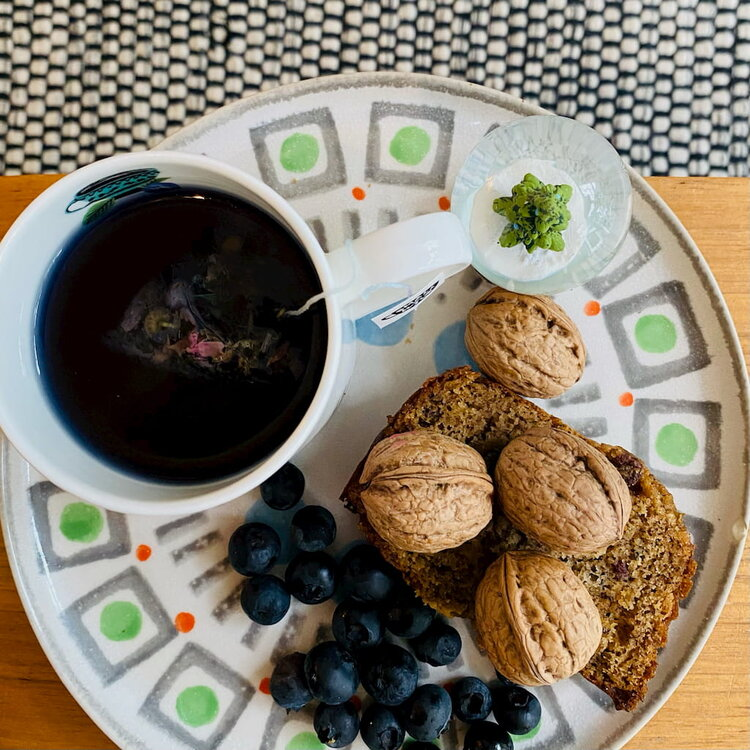 Blue tea on plate with walnuts, blueberries and banana bread