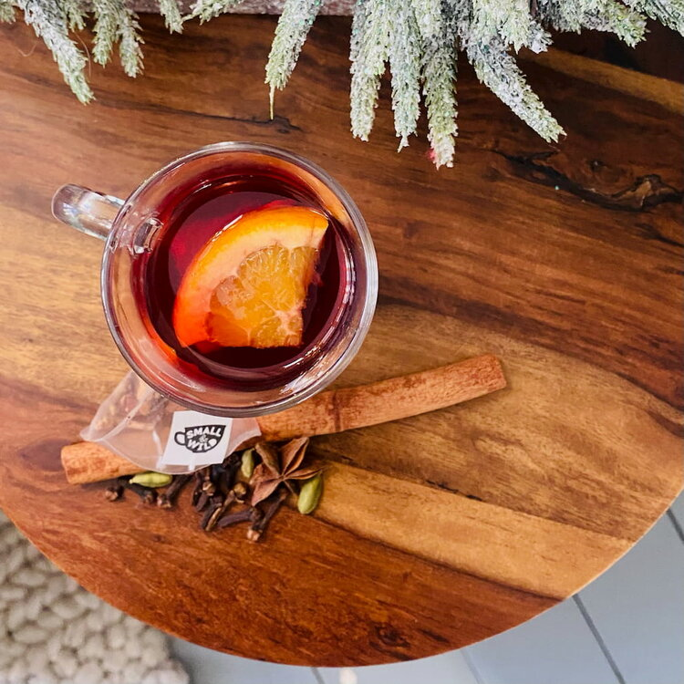 Mulled merry tiger tea with slice of orange and cinnamon stick in glass mug