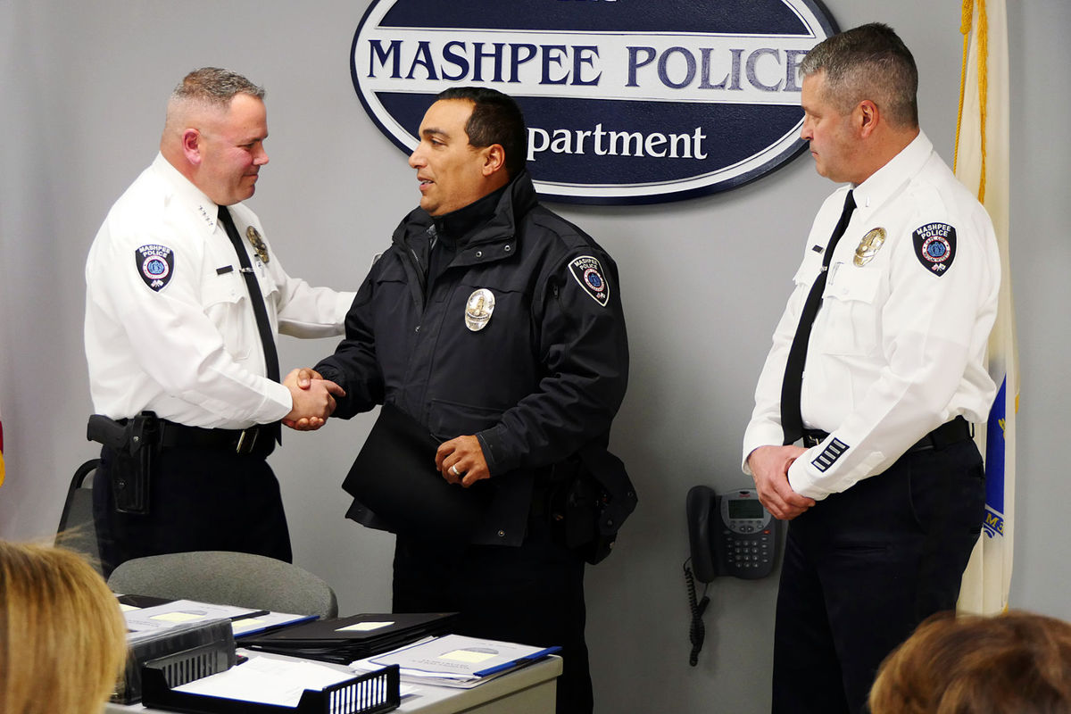 Chief Scott Carline congratulates officer Kevin Frye after presenting him with the distinguished service medal, as newly promoted Lieutenant Olivier Naas looks on. Officer Frye has served with the Mashpee Police Department for 24 years.