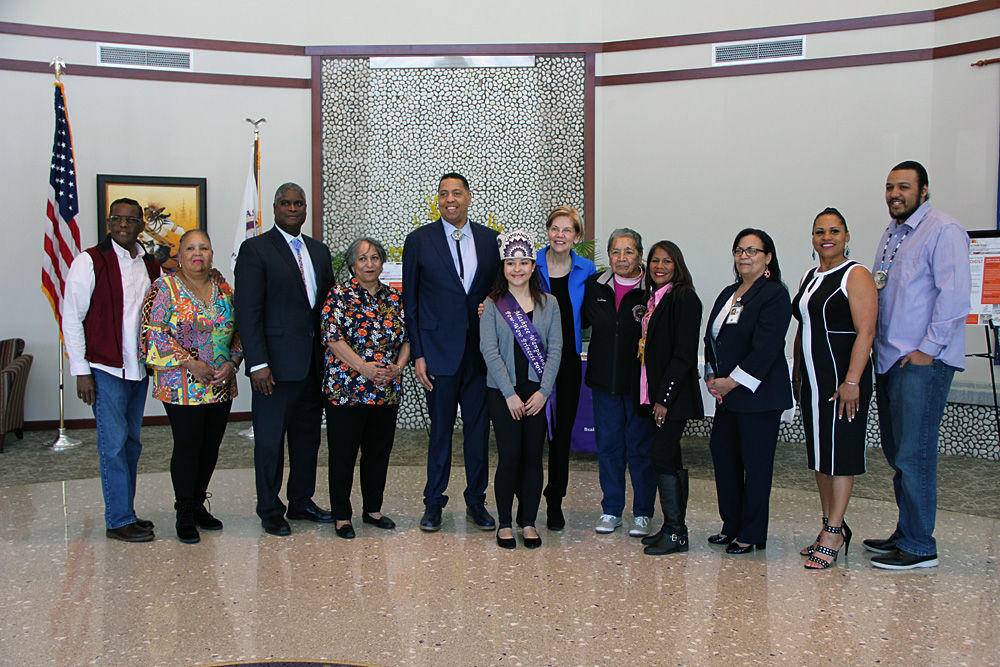 Senator Elizabeth Warren (center, in blue jacket), poses with members of the Wampanoag Tribe during her visit to the Wampanoag Health Unit on April 21. Pictured from left to right are: Medicine Man Earl (Soaring Eagle) Cash Jr.; Ann Marie Askew; tribe treasurer Gordon Harris; tribal councilwoman Yvonne Avant; Mashpee Wampanoag Tribal Council chairman Cedric Cromwell; Chenoa Peters; Senator Warren; Pauline Peters; Winnie Johnson-Graham; Rita Consalvos; Cheryl Frye-Cromwell; and Brian Weeden.