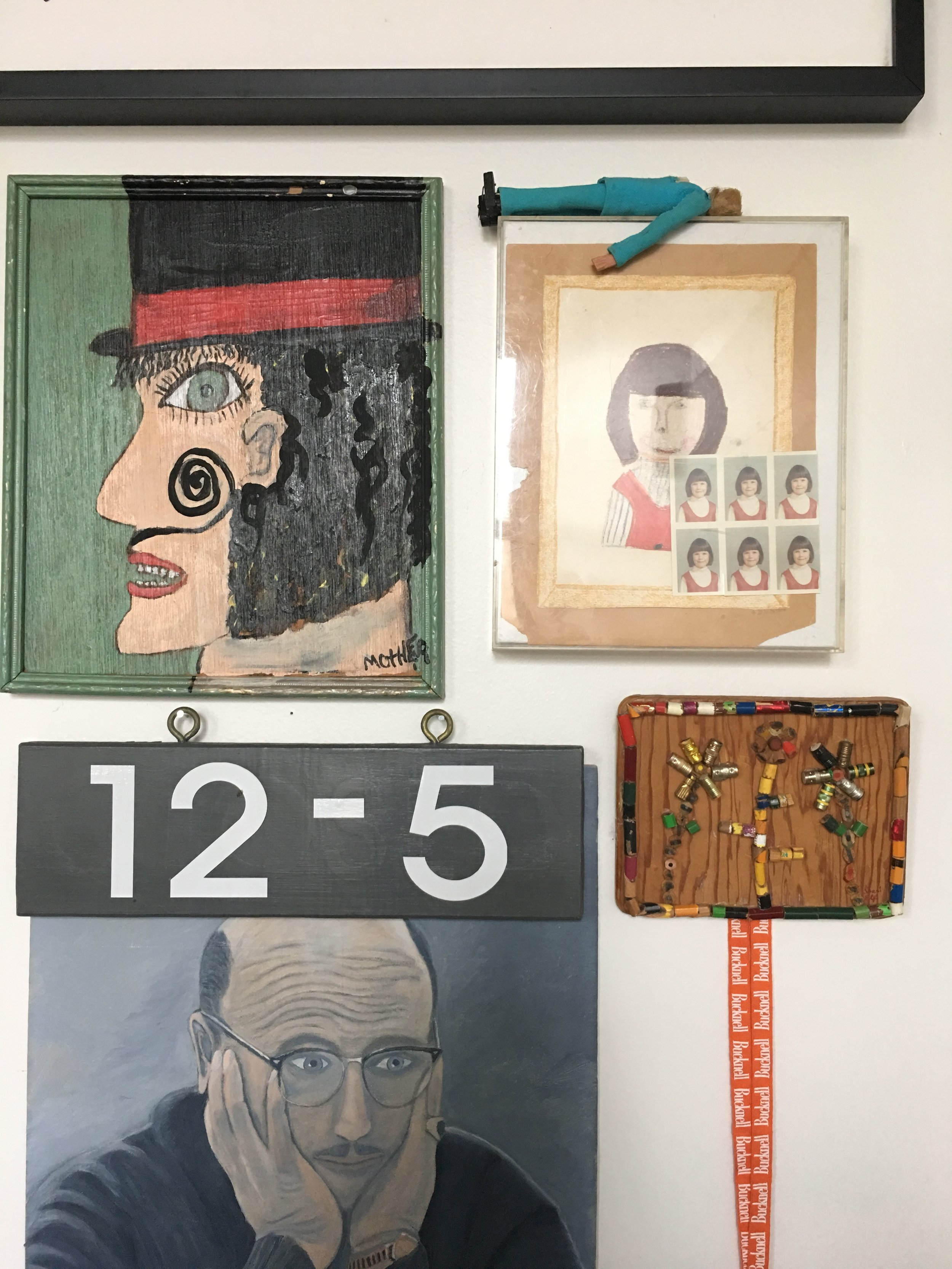 A gallery wall in the library includes an amazing combination of works including family pieces and fun objects like the little man in the blue suit above a childhood self portrait.