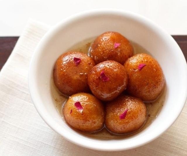 Gulab jamun in a white bowl with garnish