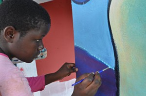 Students add their own touches to the mural