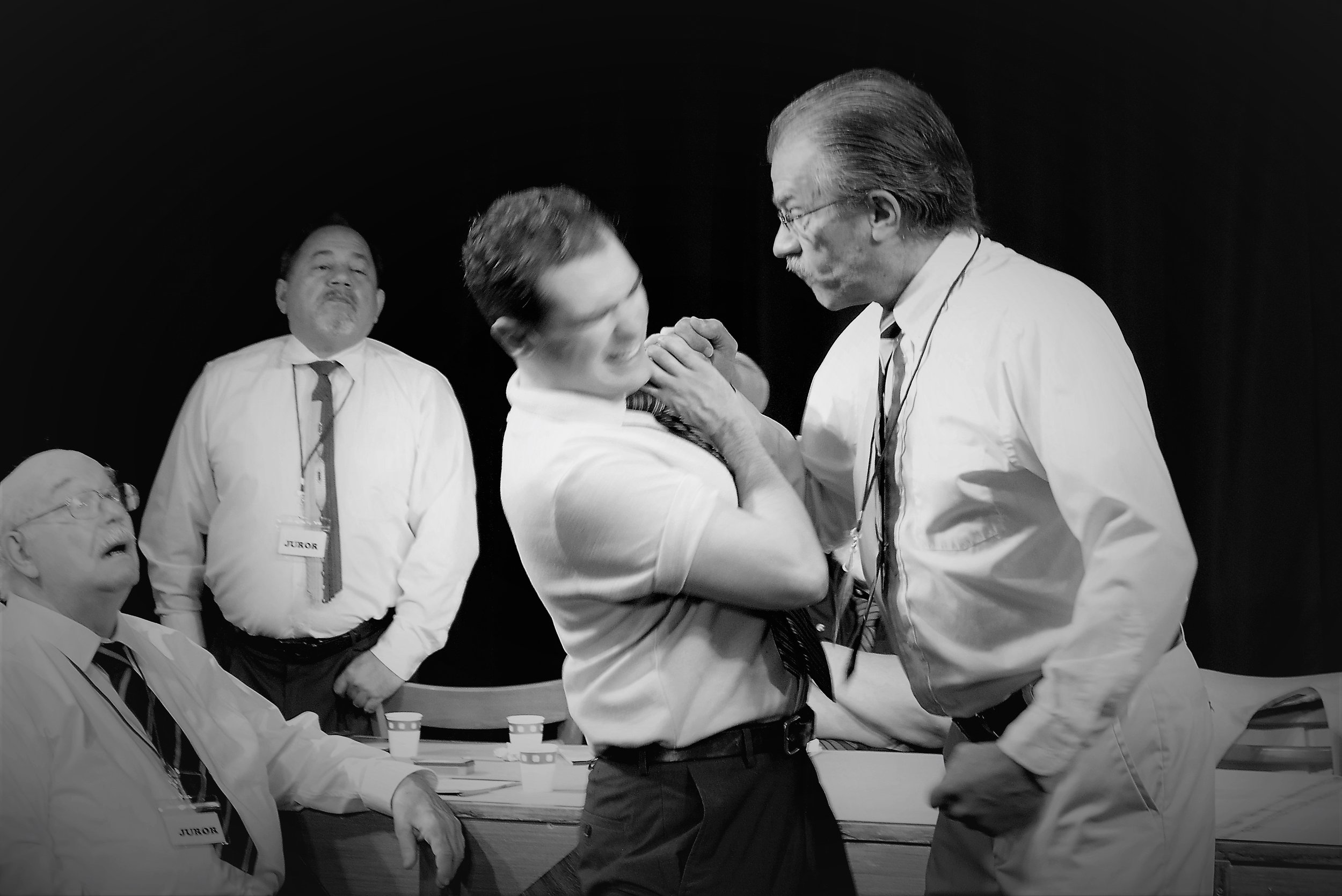 Jurors 9 and 11 (Doug Smedbron and Erico Ortiz), from left, watch as Jurors 5 and 4 (Zach Sharrock and Pau Weir) re-enact a murder in a scene from Cream City Theater's '12 Angry Men.'