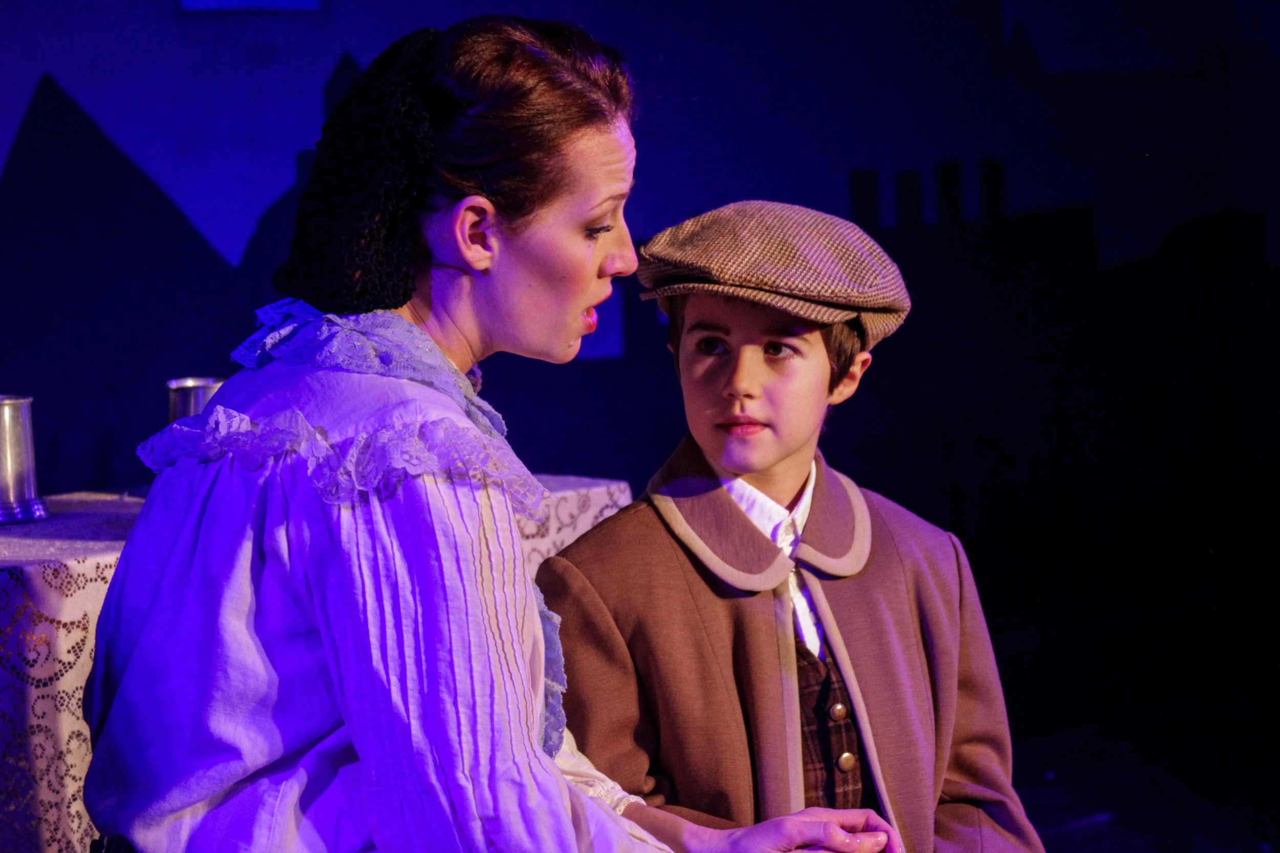 """Mrs. Cratchit (Cayla Anderson) sings to Tiny Tim (Tyler Earnest) the tender song """"The Winter Will Soon Be Over"""" in a scene from Lake Country Playhouse's 'A Christmas Carol."""""""