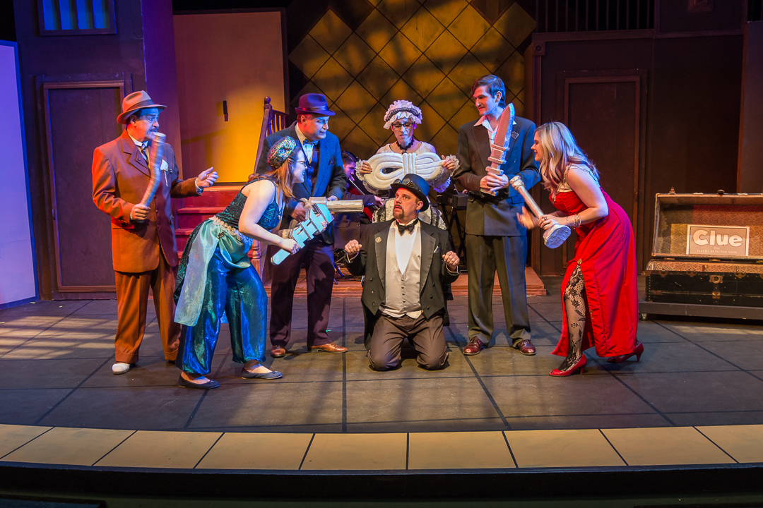 """Six murder suspects, each holding a possible murder weapon, surround Mr. Boddy (Mike Owens) in a scene from Waukesha Civic Theatre's """"Clue: The Musical."""" Pictured, from left, are Colonel Mustard (David Jirik), Mrs. Peacock (Margaret Teshner), Professor Plum (Andrew Byshenk), Mrs. White (Laura Heise), Mr. Green (Thomas Hess) and Miss Scarlet (Rachel Krause)."""