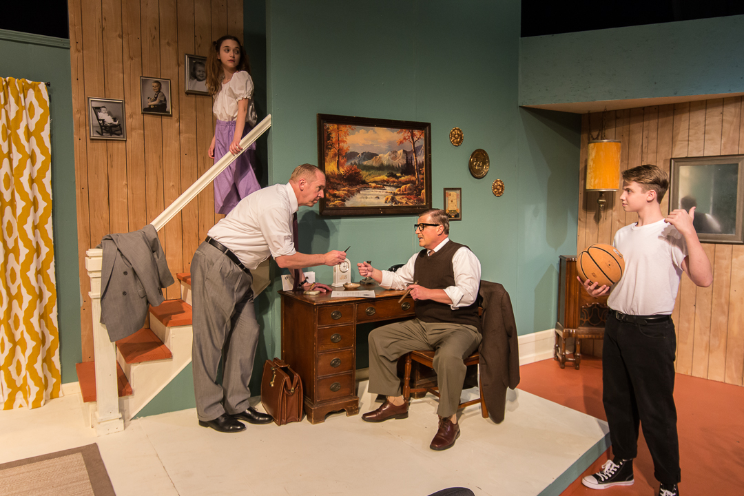 "Jim Anderson (Thomas Van Gilder) hands a pen to Mr. Brinksworth (Jim Stahl) for him to sign an insurance contract while Kathy (Julia Rady) and Bud (Alec Anderson-Conlon) look on in a scene from Waukesha Civic Theatre's ""Father Knows Best."""
