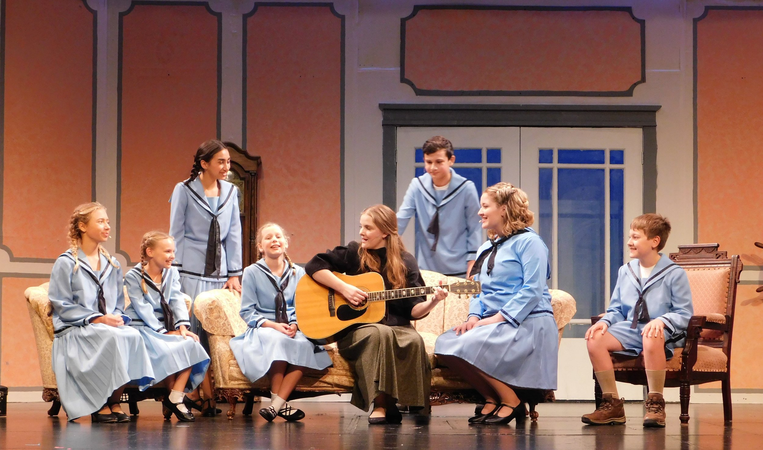 "Maria (Susannah Thorngate) gives a music lesson surrounded by the von Trapp children, from left, Brigitta (Lilli Graesing), Gretl (Anna Gerke), Louis (Hannah Filter), Marta (Natalie Krogwold), Frederich (Aaron Economy), Liesl (Sarah Melcher) and Kurt (Mitchell Anderson) in a scene from West Community Theatre's ""The Sound of Music."""