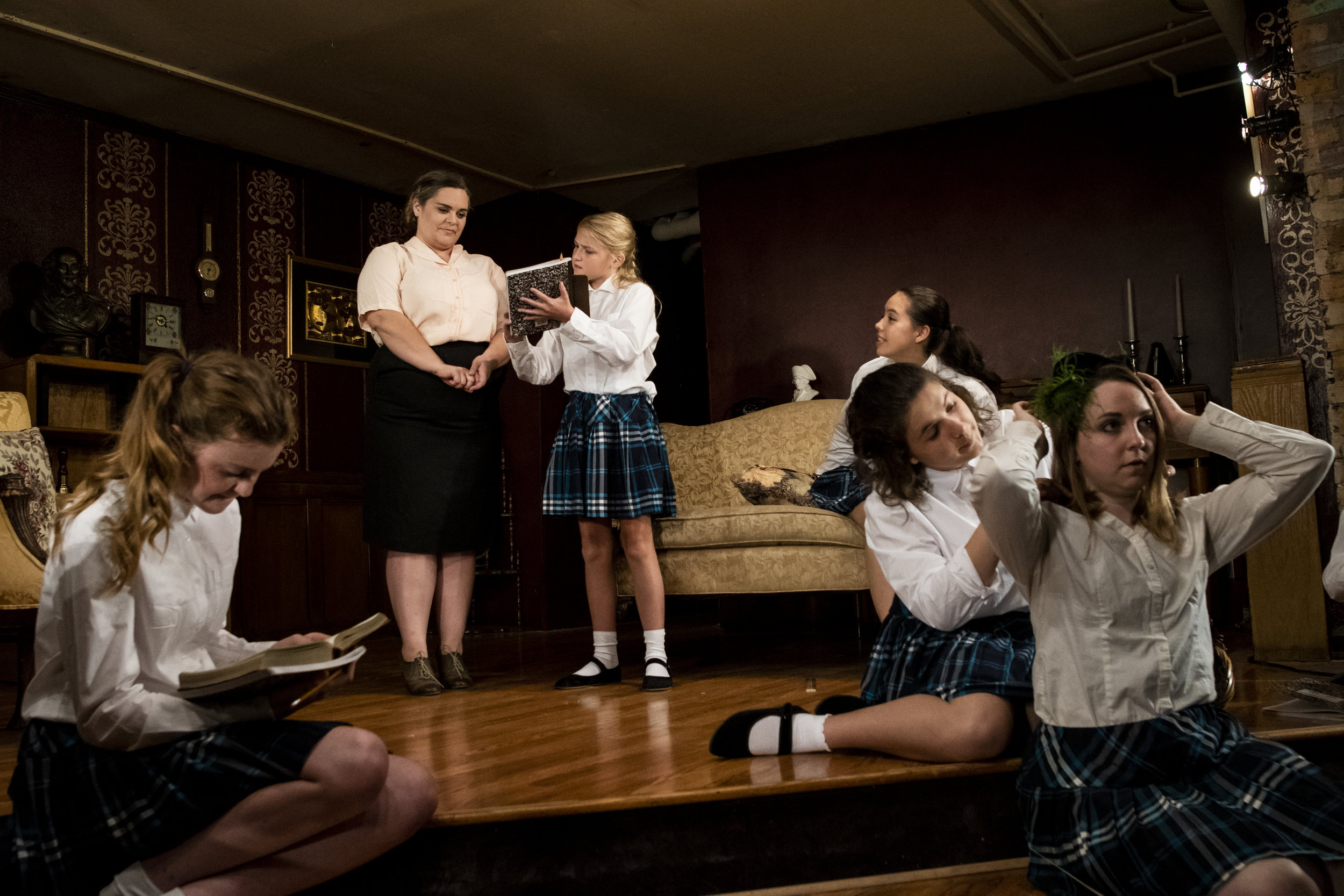 "Mrs. Lily Mortar (Brittany Boeche) discusses literature with student Catherine (Ellie Boyce) while her classmate Helen (Madie Gellings) listens on the couch in a scene from Outskirts Theatre Company's ""The Children's Hour."". In front, from left, are students Peggy (Greta Dane), Evelyn (Katrina Liberman) and Rosalie (Anna Lee Murray)."
