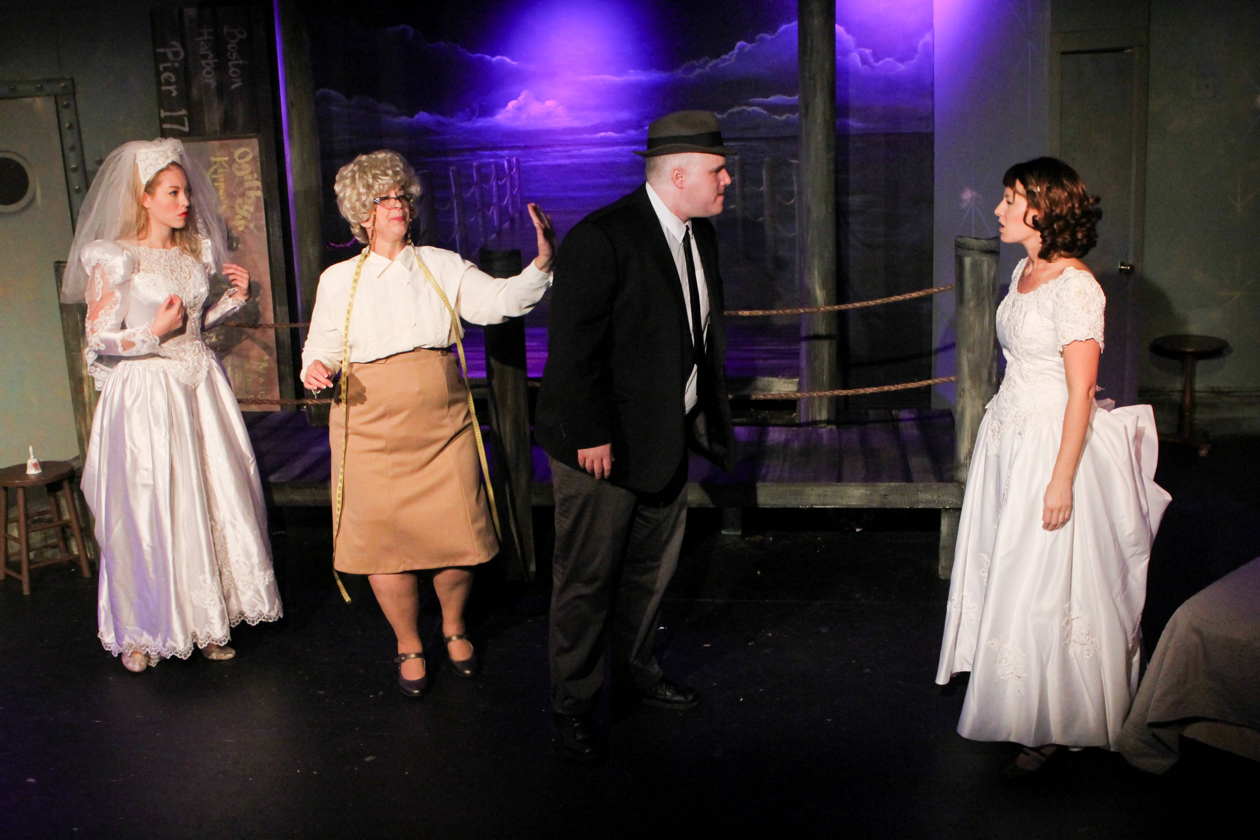 """G-man Frank (John Reilly) confronts his fiancé Maggie (Cayla Anderson) at a dress shop where Lynn (Stephanie Nilsen) is also trying on dresses suggested by the shop's owner (Rebecca Richards) in a scene from Lake Country Playhouse's """"Red Herring."""""""