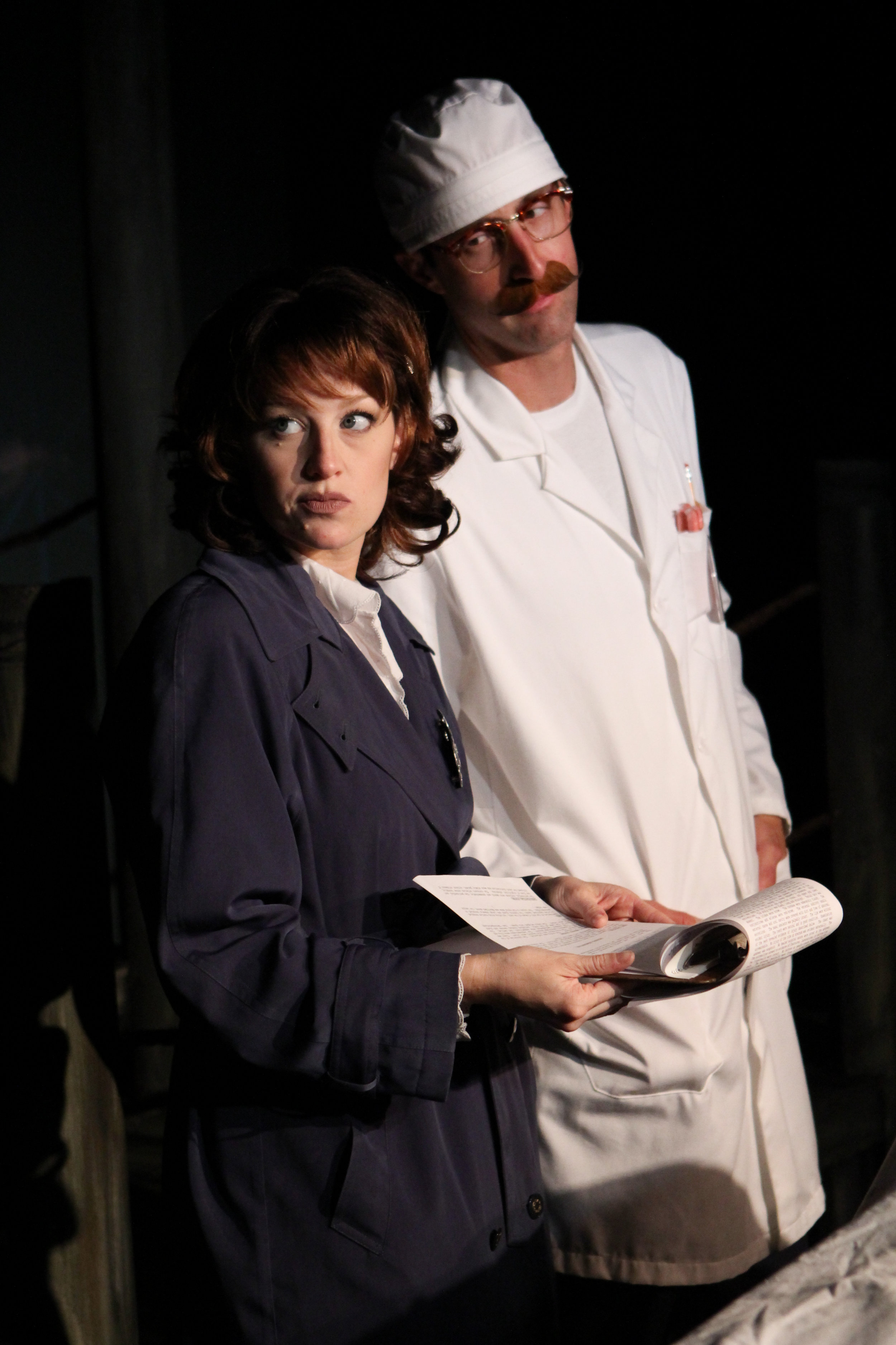 """Detective Maggie (Cayla Anderson) and the coroner (Dustin Nolan) compare notes during an autopsy in a scene from Lake Country Playhouse's """"Red Herring."""""""