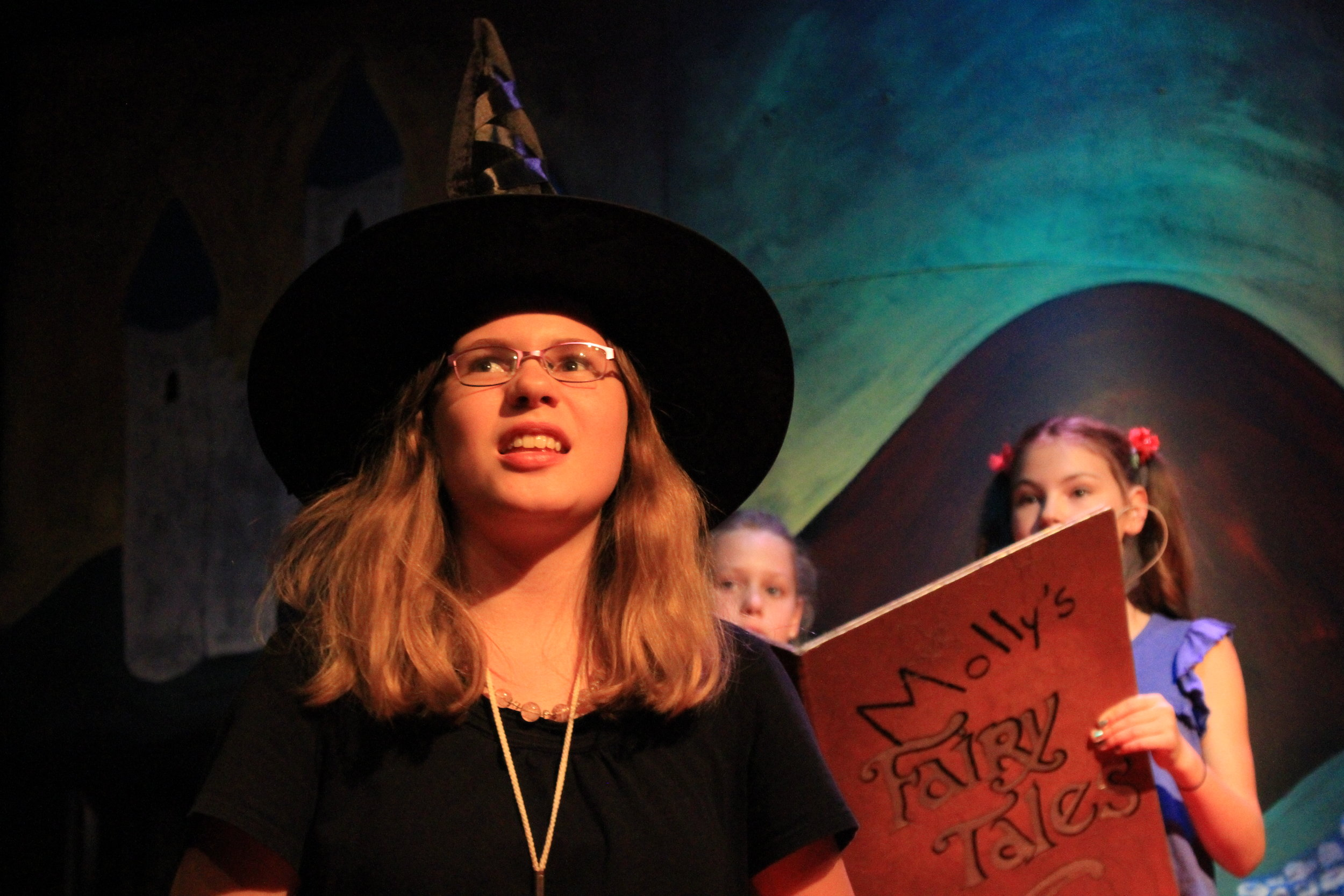 "Delaney Cowles plays a witch while Natalie Krogwold and Maya Kalush, from left, as Molly and Peaches, read from an altered book of fairy tales in The Box Theatre Co.'s ""Molly's (Mostly) Accurate Retelling of Fairtales."""