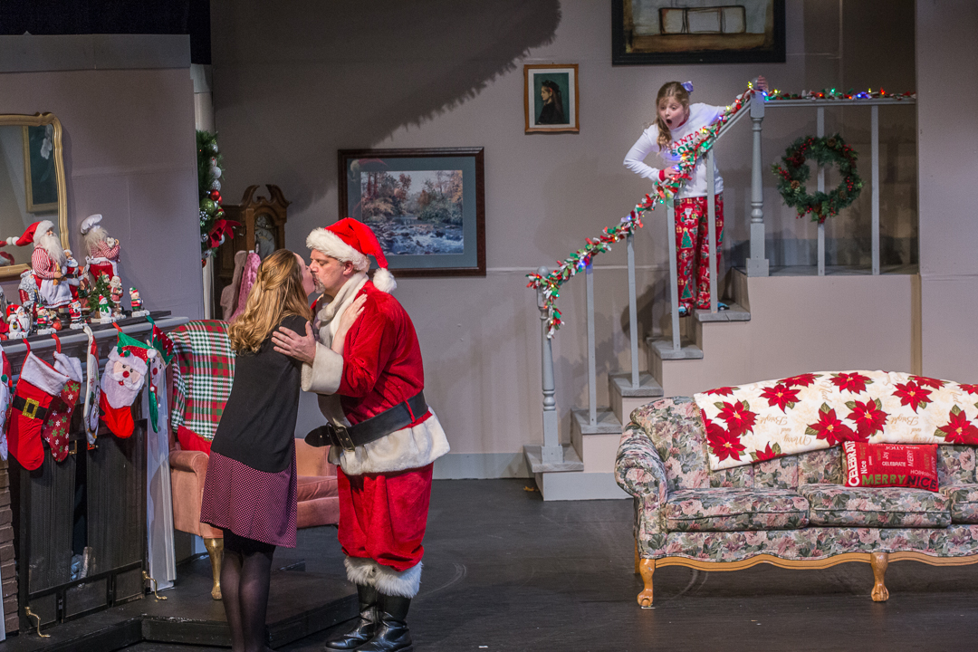 """Judy (Jen Hull Anderson) and husband Bill (Mike Anderson) are being watched by their surprised daughter Stella  (Emily McCaskey), who later joins her siblings in singing """"I Saw Mommy Kissing Santa Claus"""" during Waukesha Civic Theatre's """"Candy Cane Tales and Holiday Carols."""""""