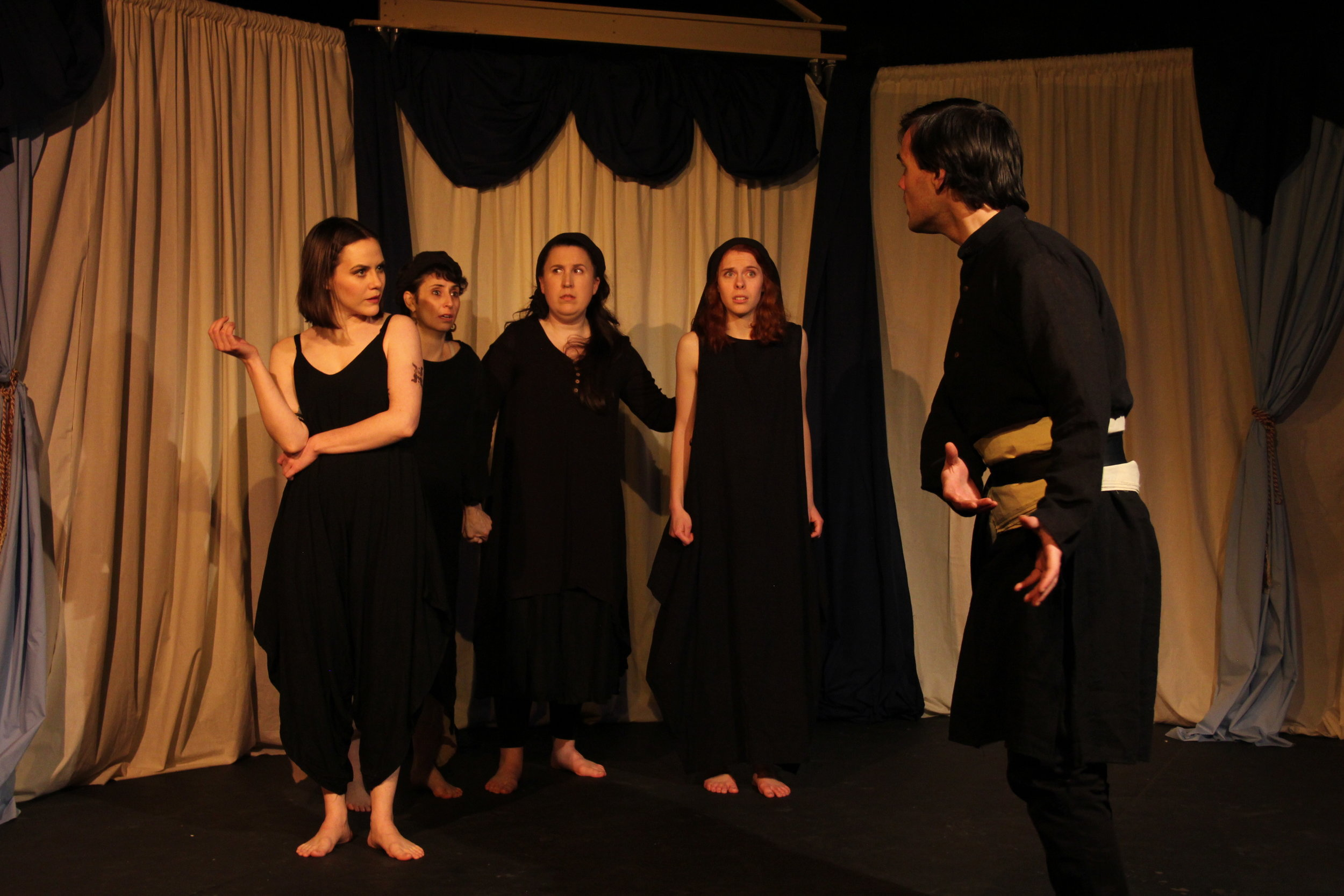 """Medea (Cara Johnston) strikes a defiant pose as she speaks to a messenger (Teddi Jules Gardener) while her friends (Abigail Stein, Madeline Wakley and Maura Atwood, from left) listen with concern in a scene from Voices Found Repertory's """"Medea."""""""